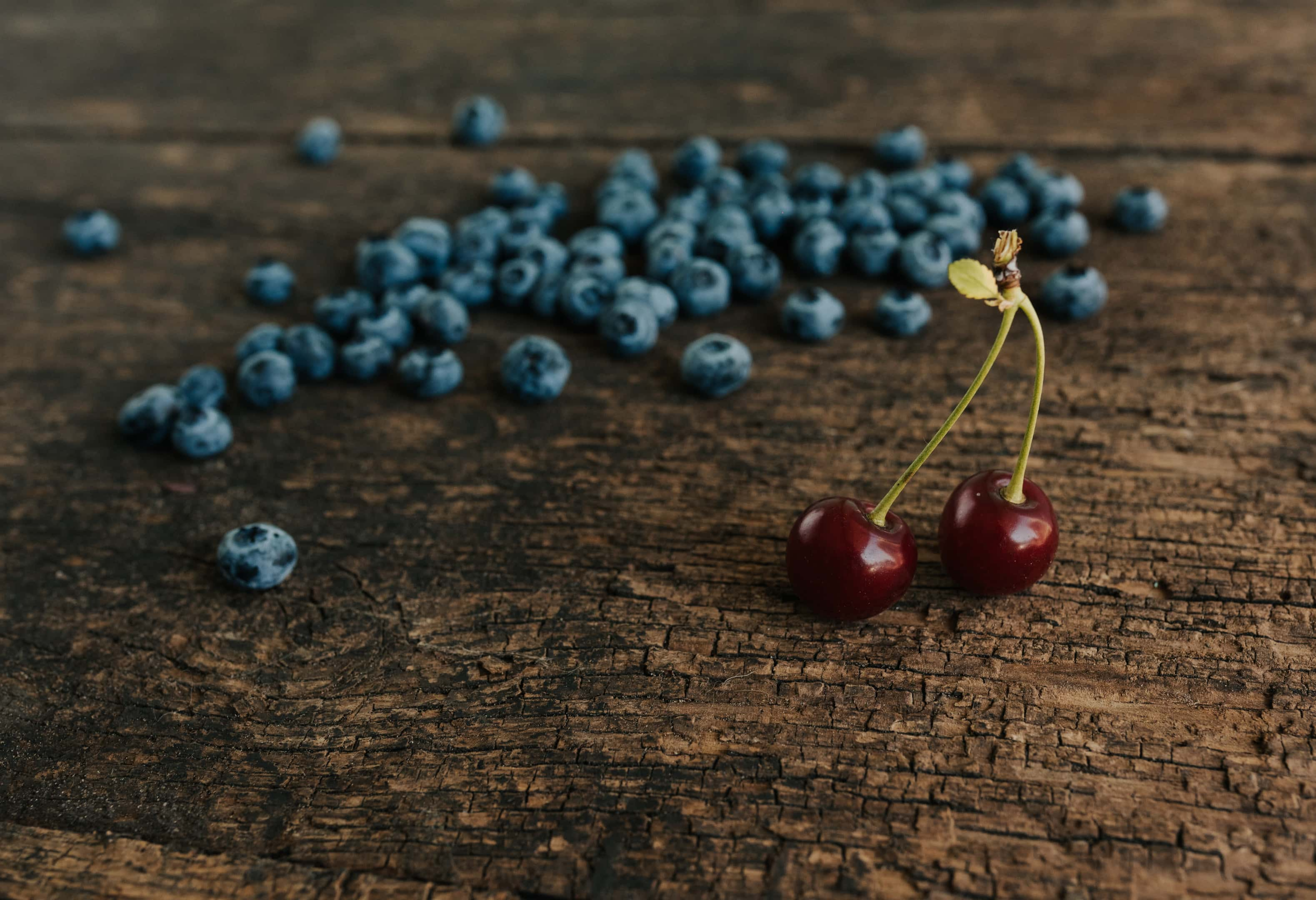 Blueberries and red cherries on wooden table