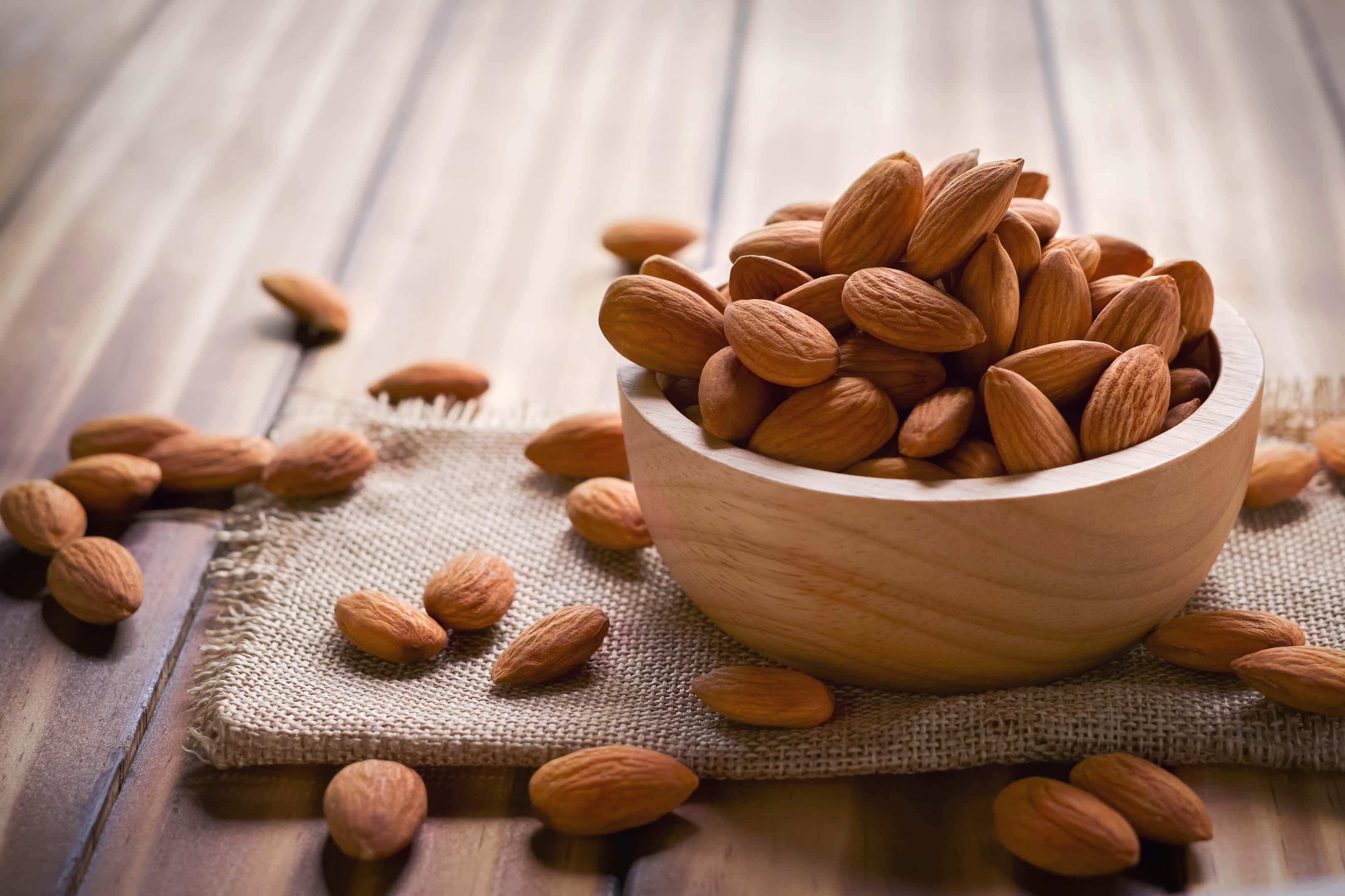 Almonds in wooden bowl on wooden table
