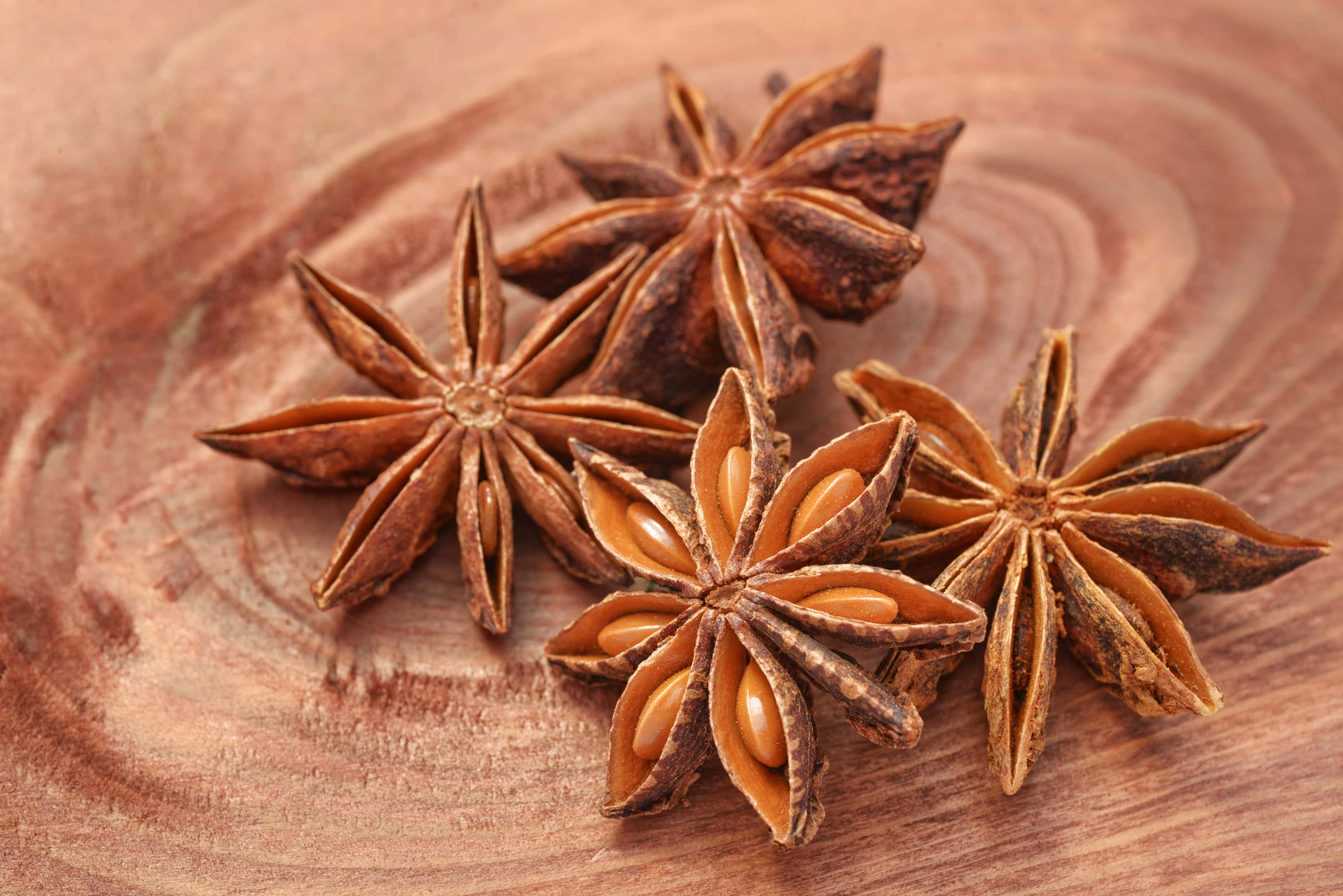 Anise star with anise seeds on wood