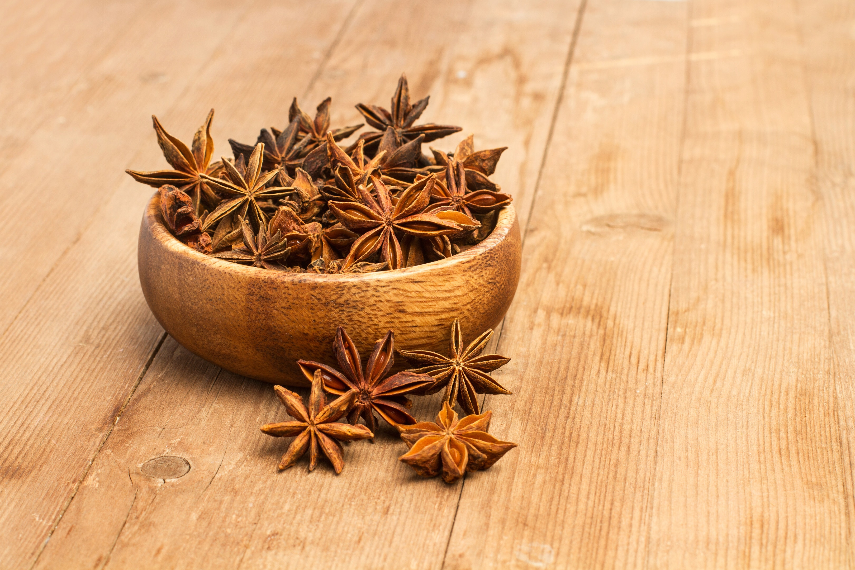 Aniseed in star anise in wooden bowl