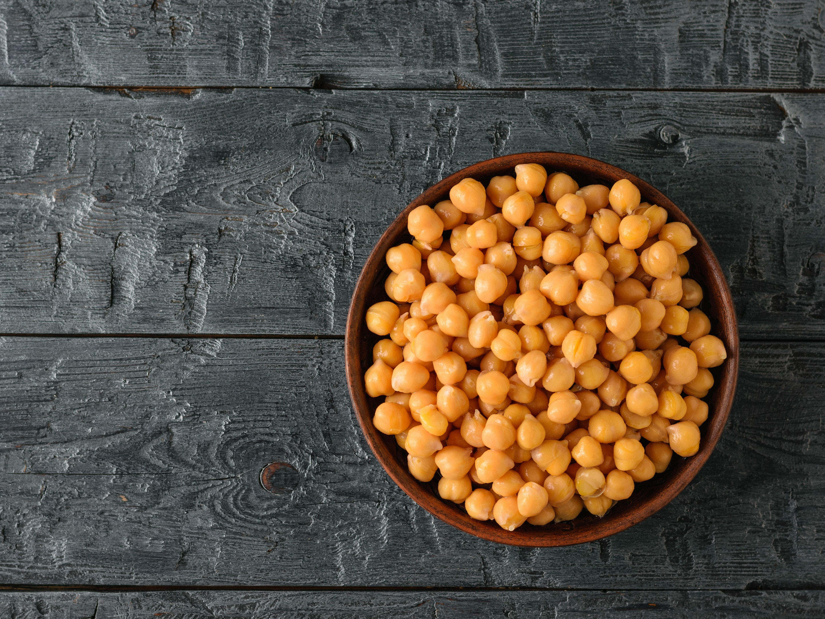 Boiled chickpeas in clay bowl on black wooden table
