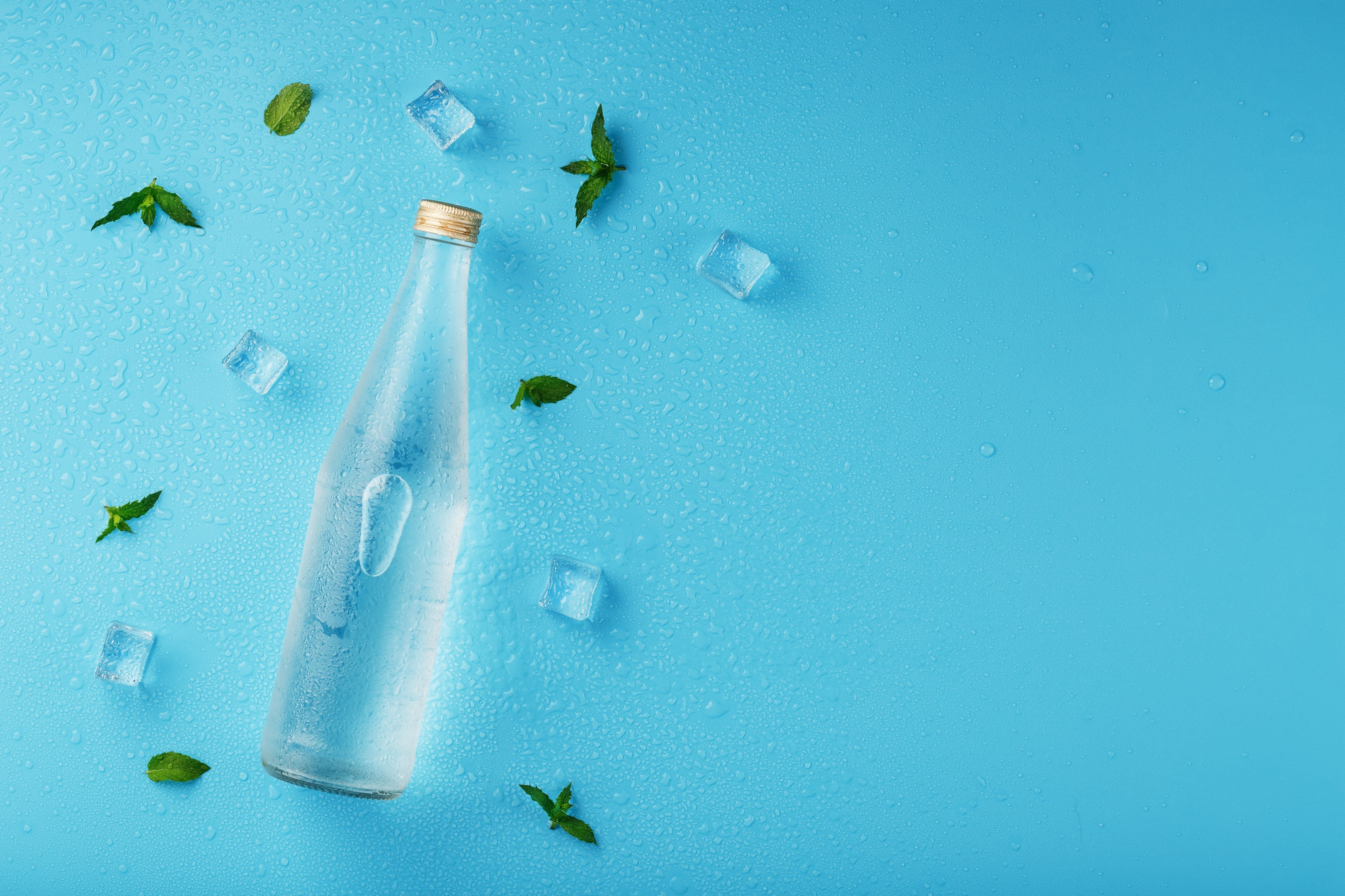 A bottle of ice water, ice cubes and mint leaves on a blue background.