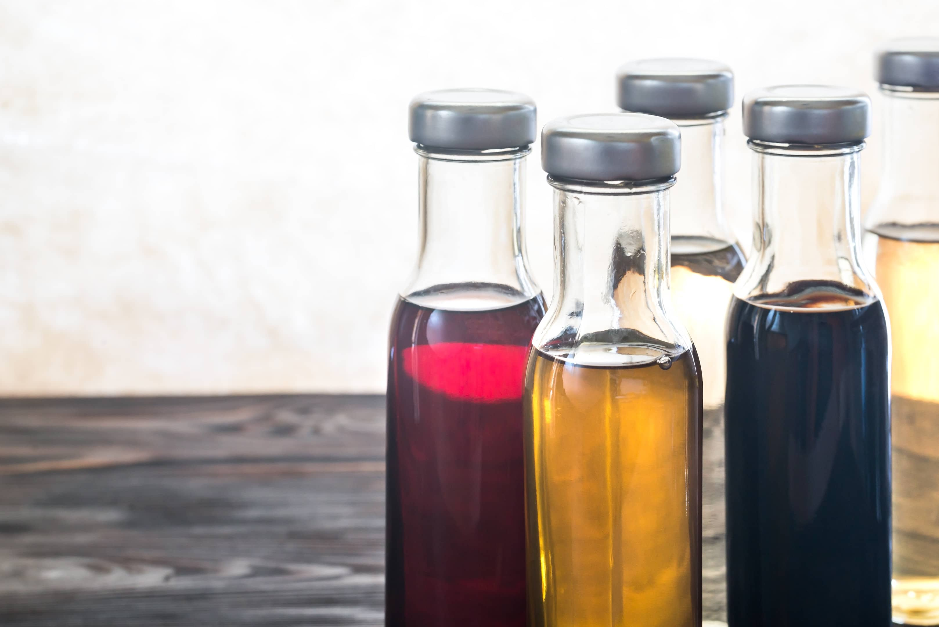 Bottles with different kinds of vinegar on wooden table