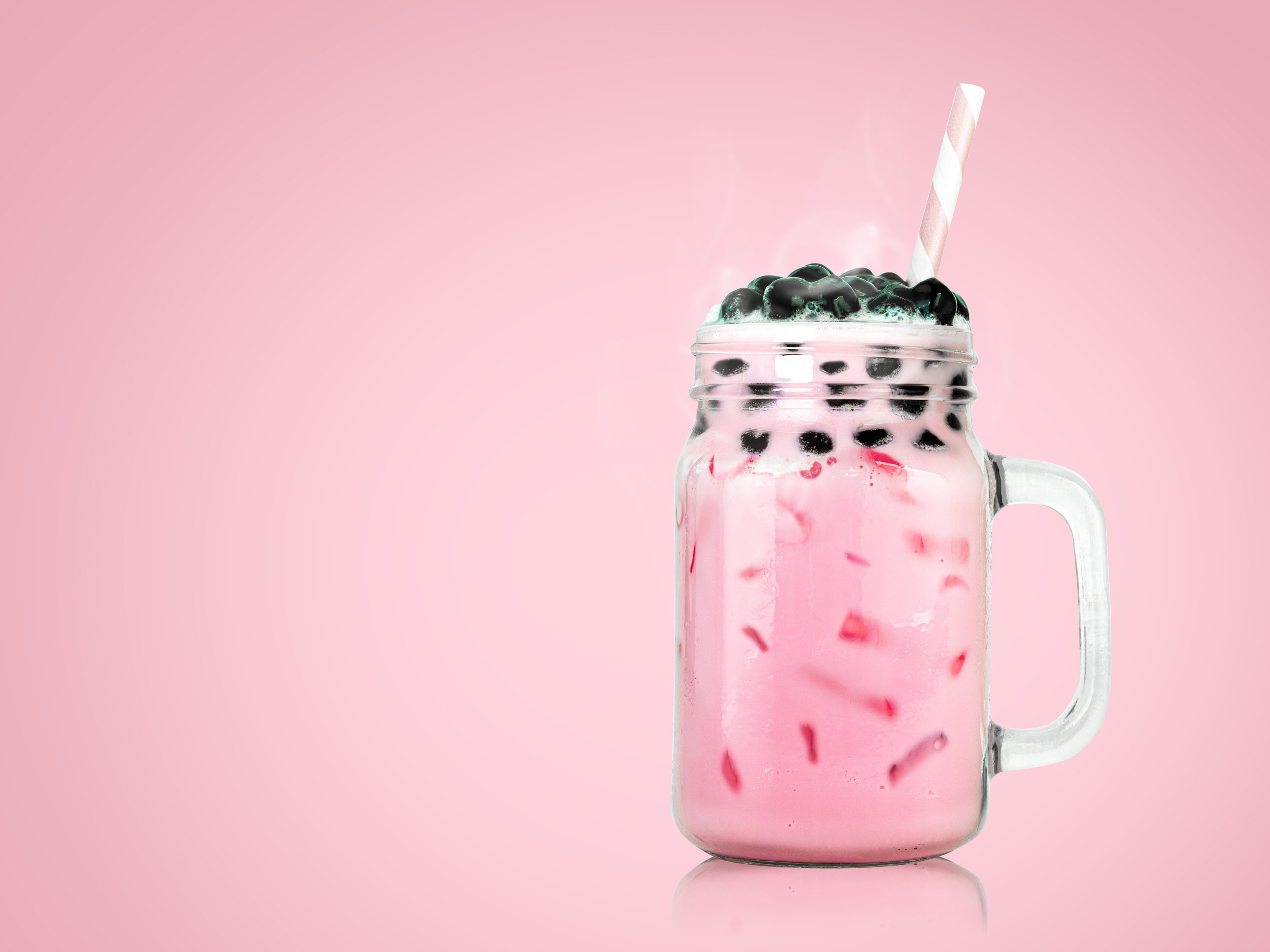 Bubble tea in clear glass on pink background