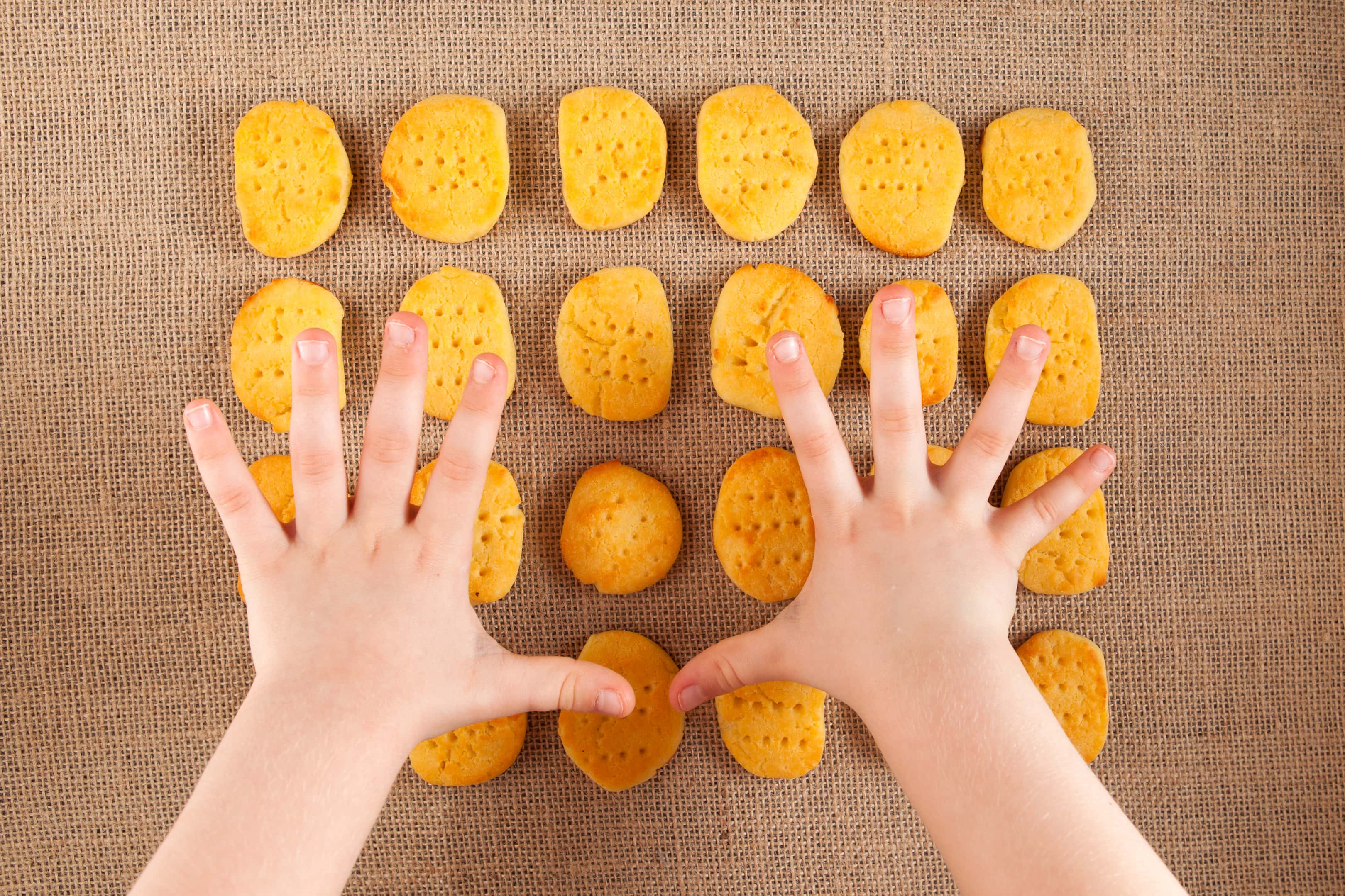 Child's hands reach for Chickpea Flour Biscuits - Vegan and Gluten-Free.