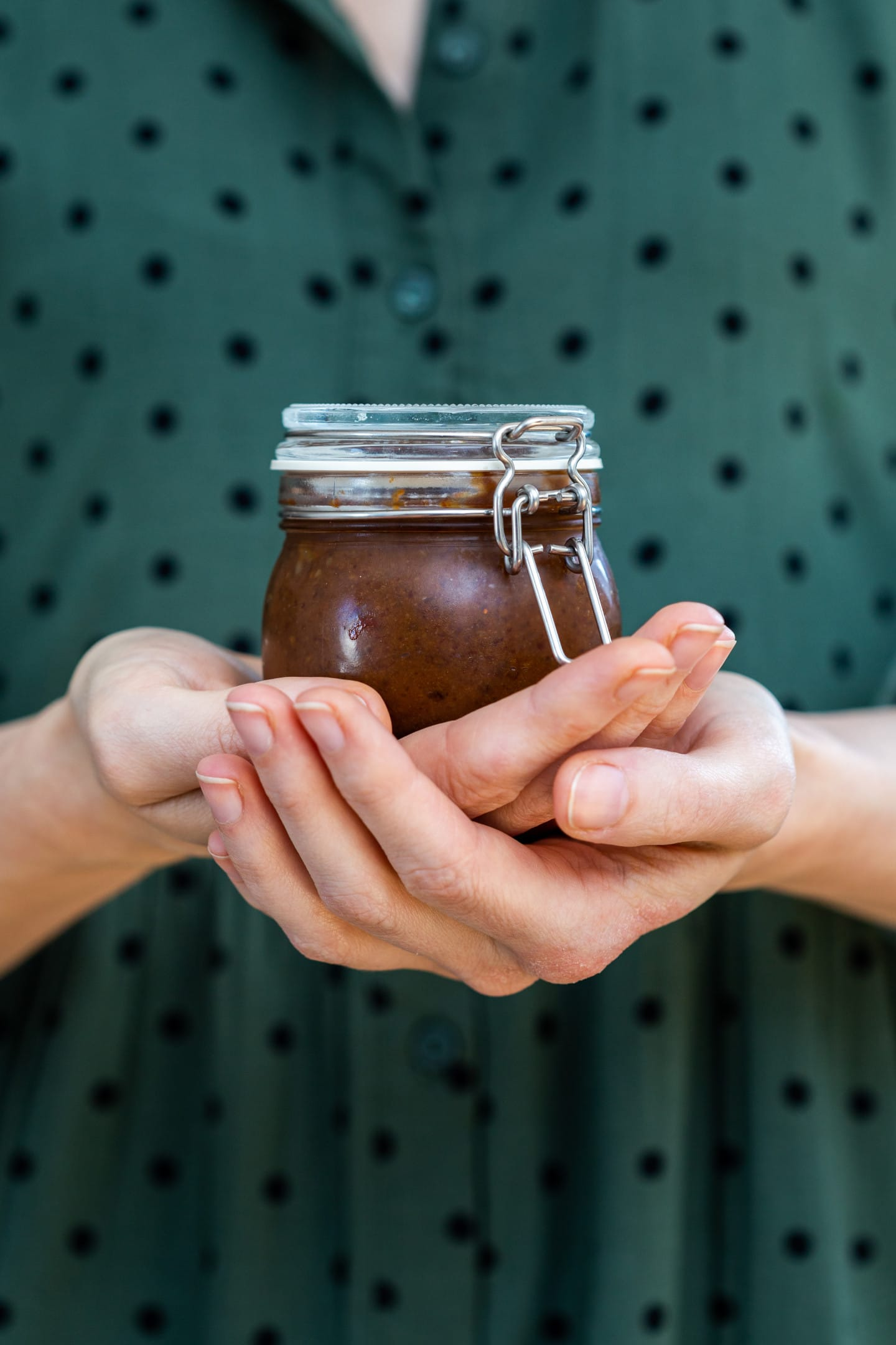 Female hands holding homemade tamarind paste jar