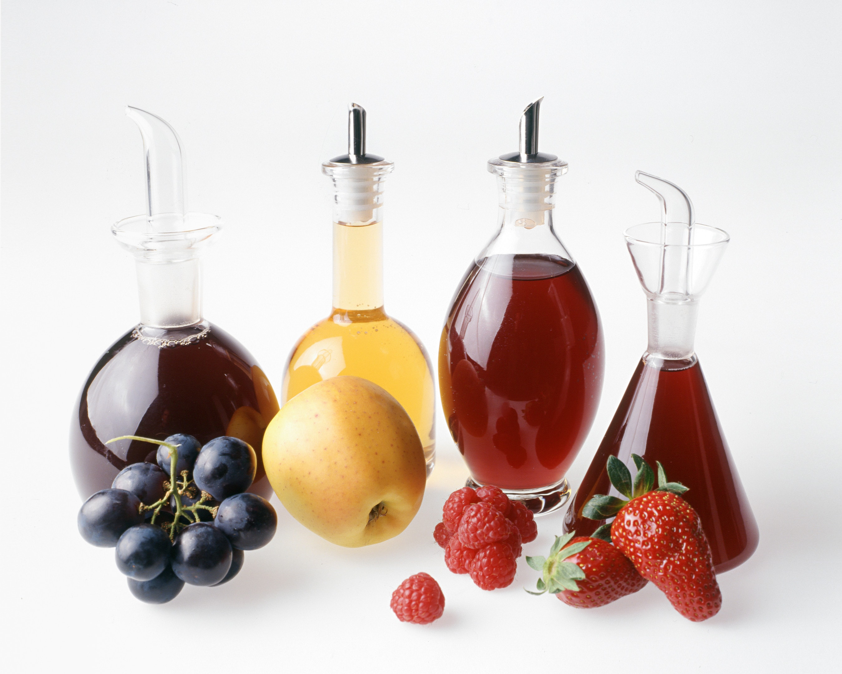 Four fruit vinegars bottles white background