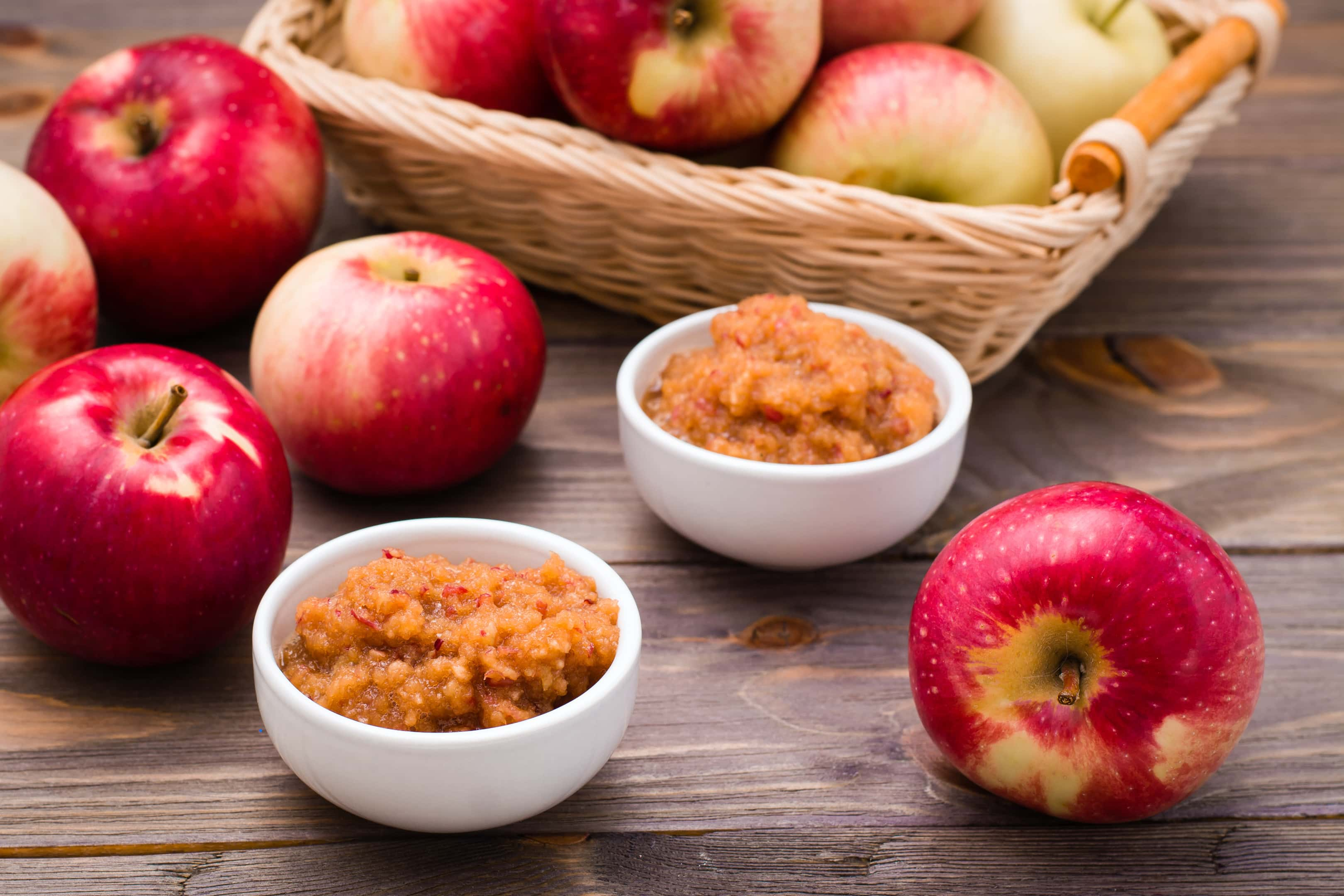 Fresh applesauce in bowls with fresh red apples on a wooden table