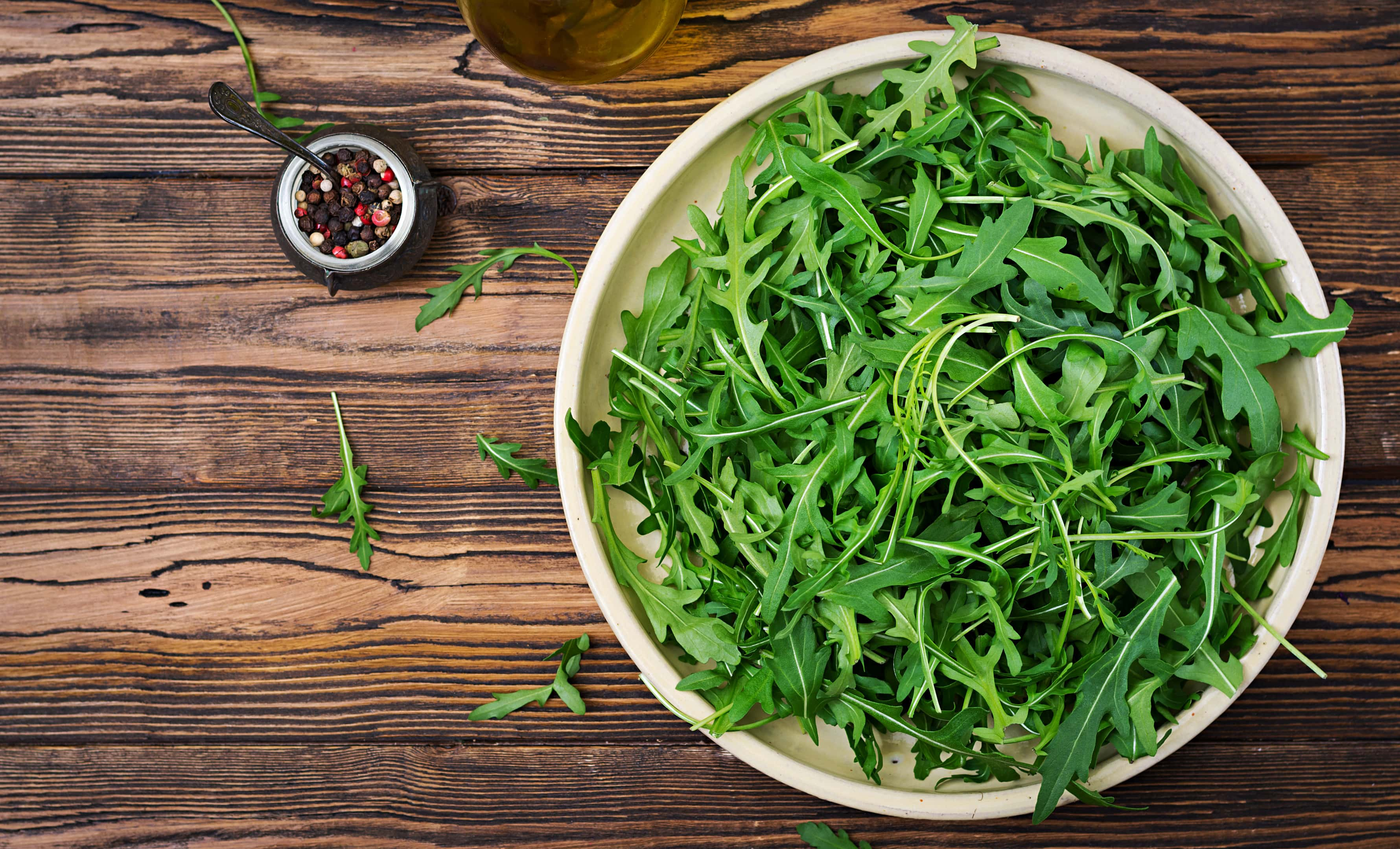 Fresh arugula leaves in a white bowl on a wooden table