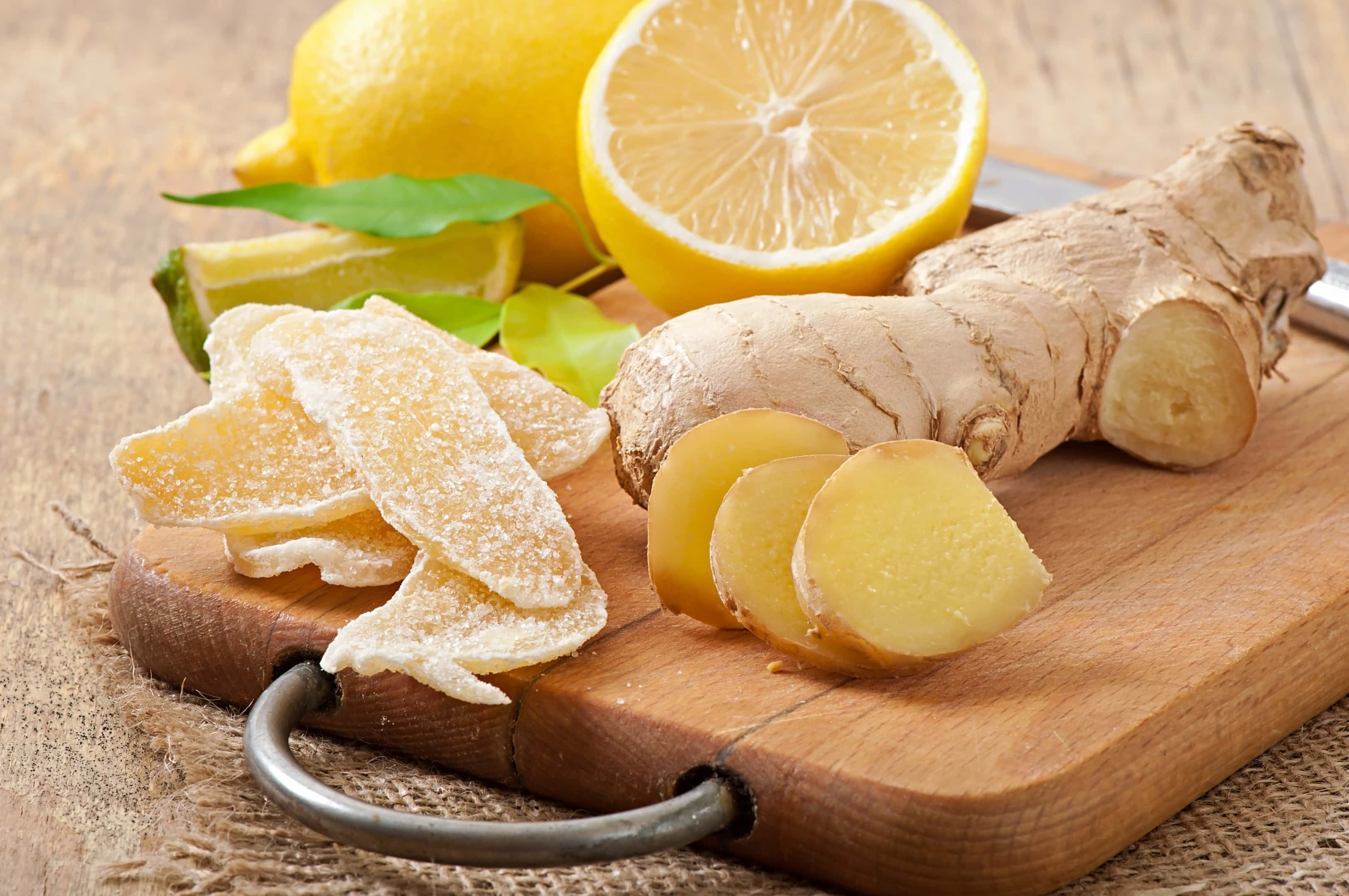 Fresh ginger root and candied ginger on wooden board