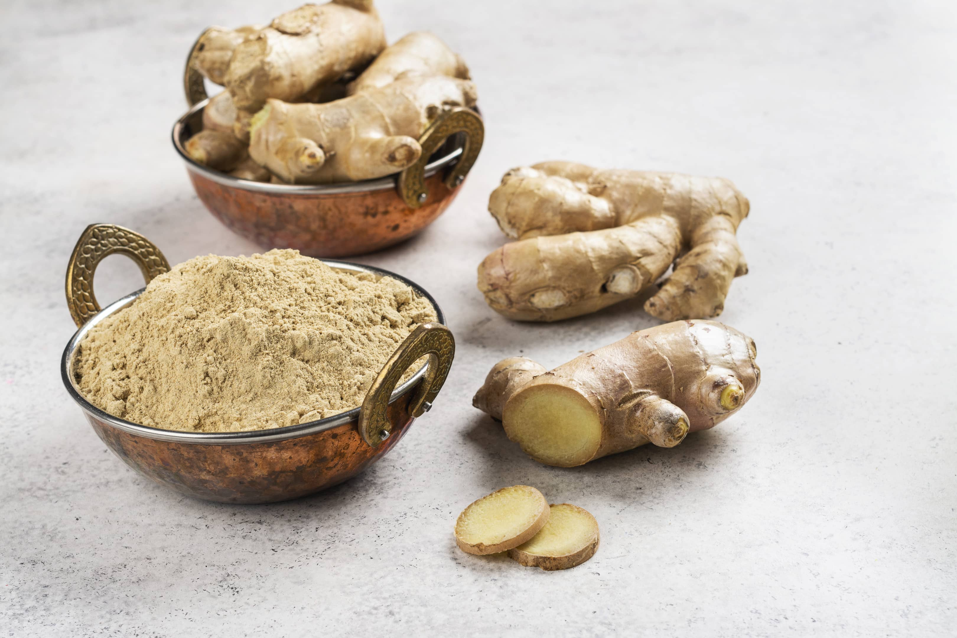 Fresh ginger root and ginger powder in copper bowl