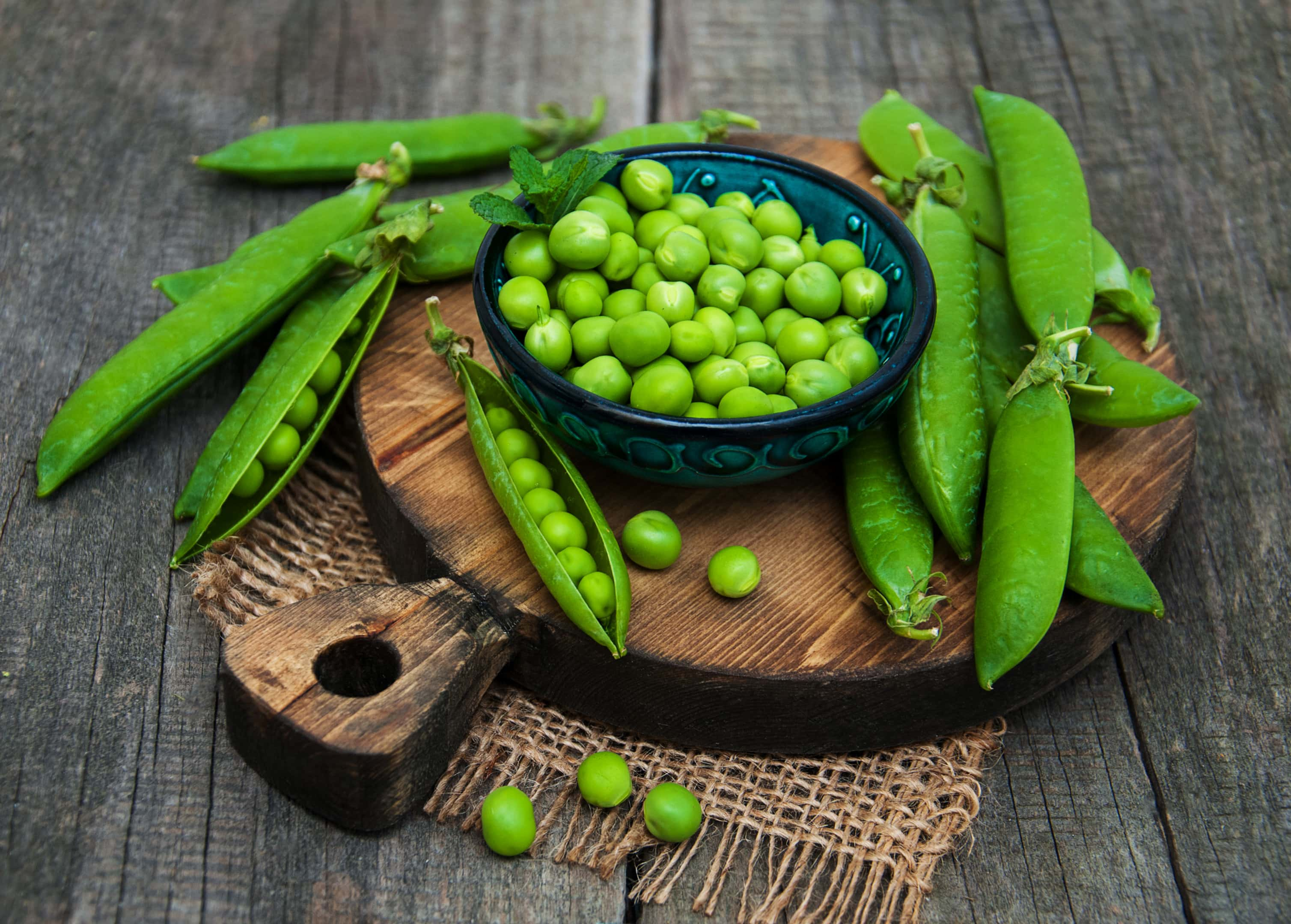Fresh green peas on wooden board