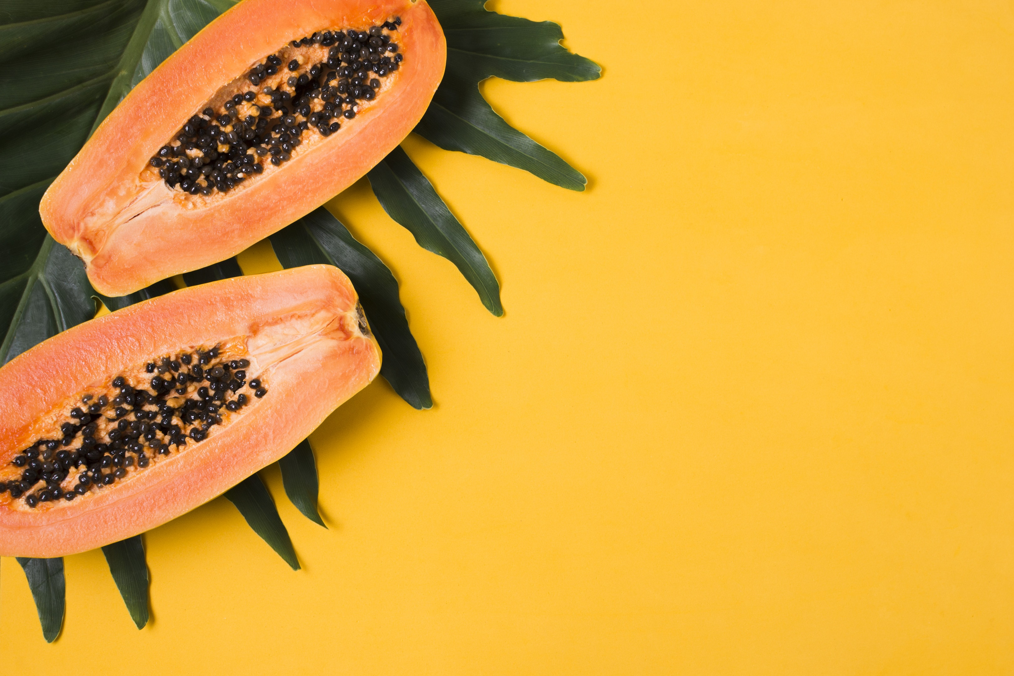 Fresh papayas on yellow background