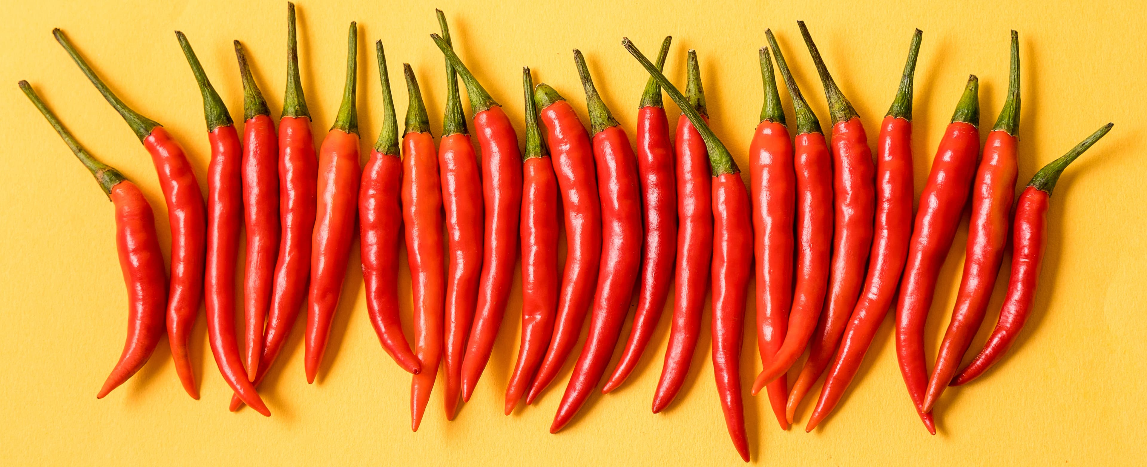 Fresh red thai peppers on yellow background