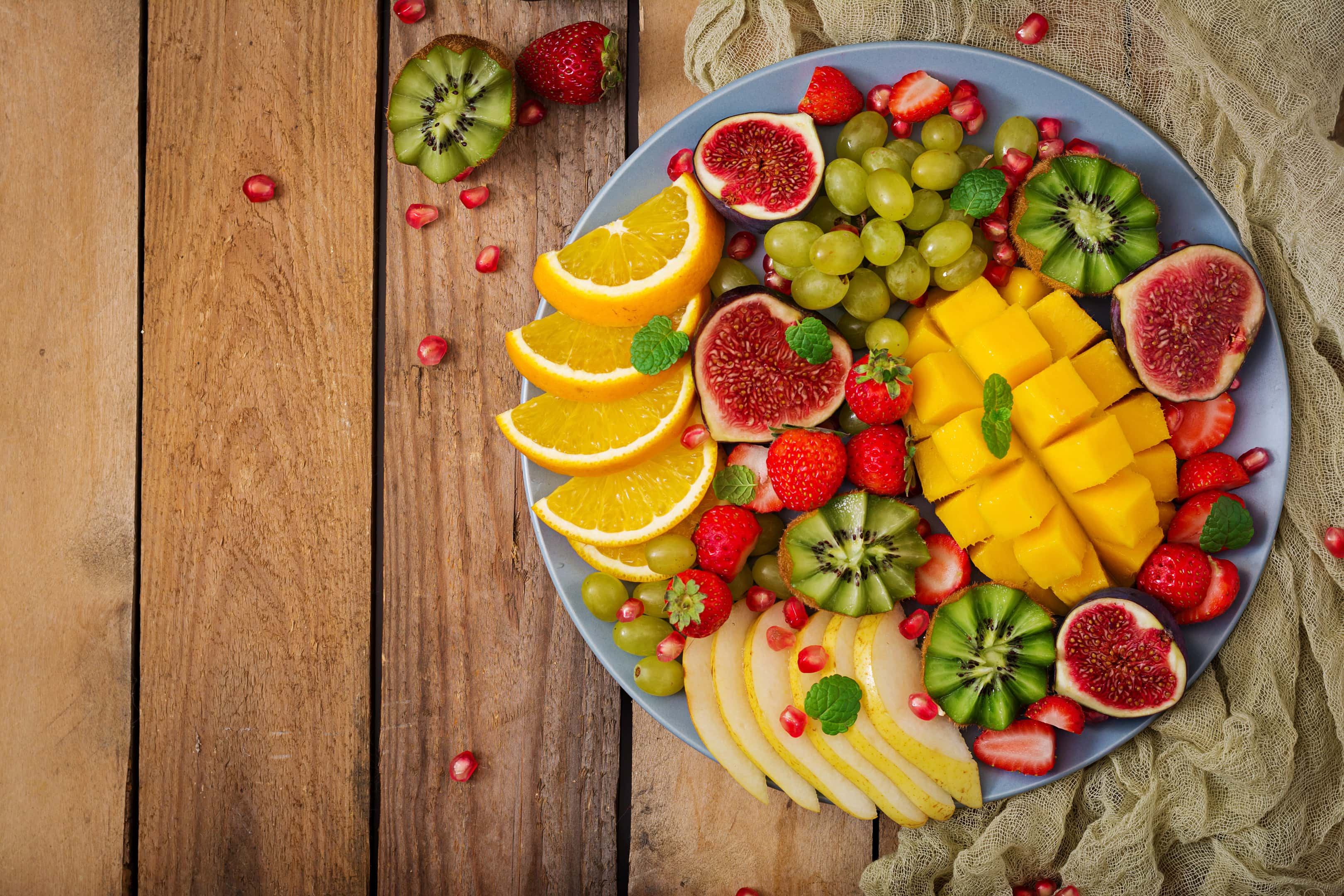 Platter of fruits and berries. Mango, kiwi, fig, strawberry, grapes, pear and orange.