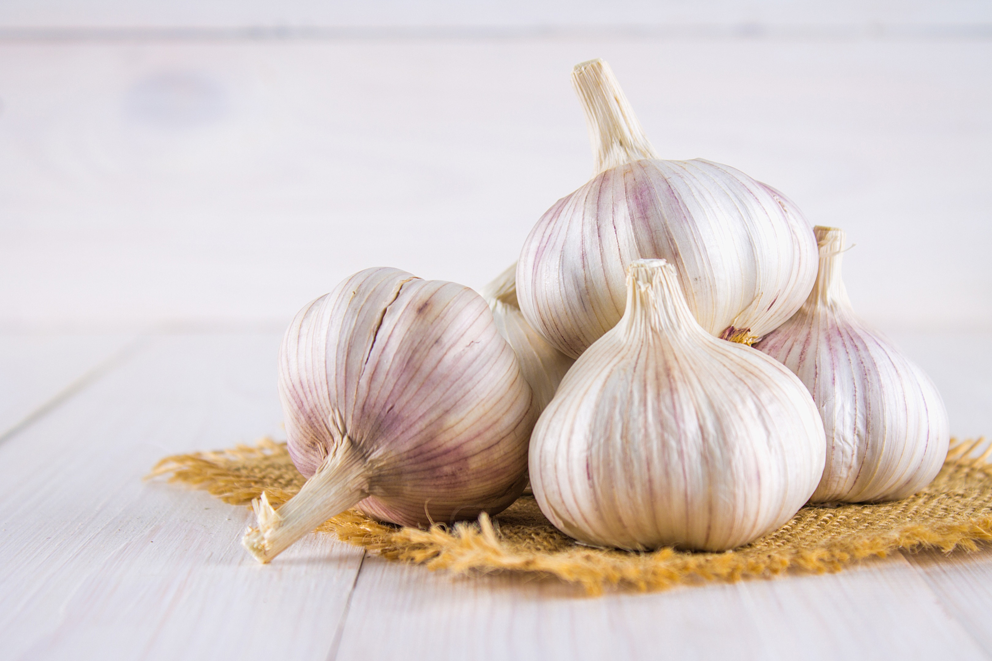 Garlic cloves on white wooden table