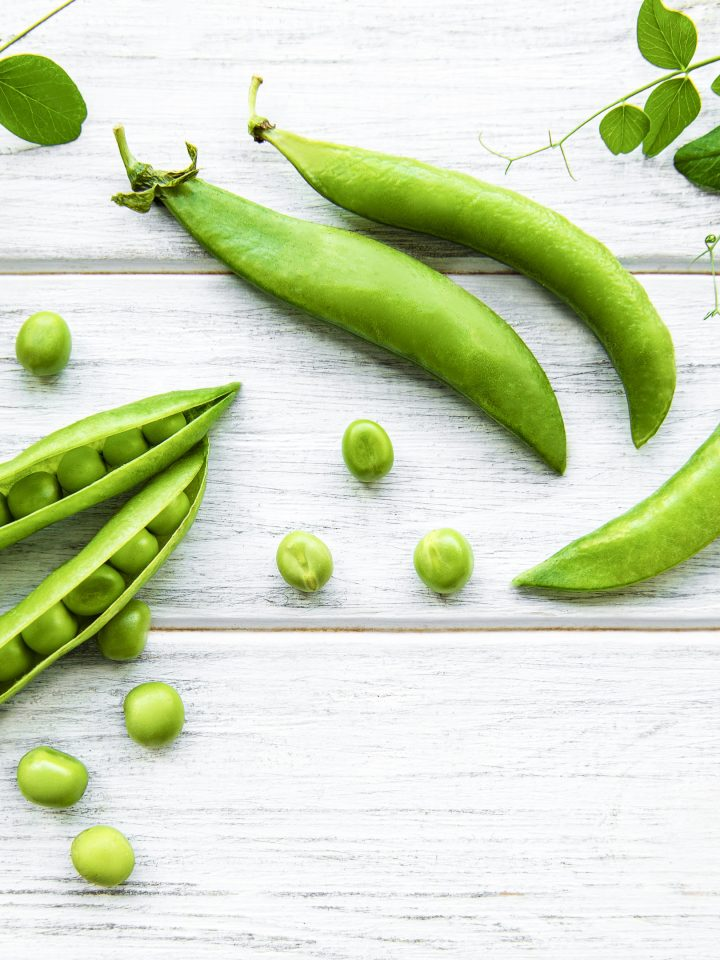 Green peas and pea pods on white wooden background