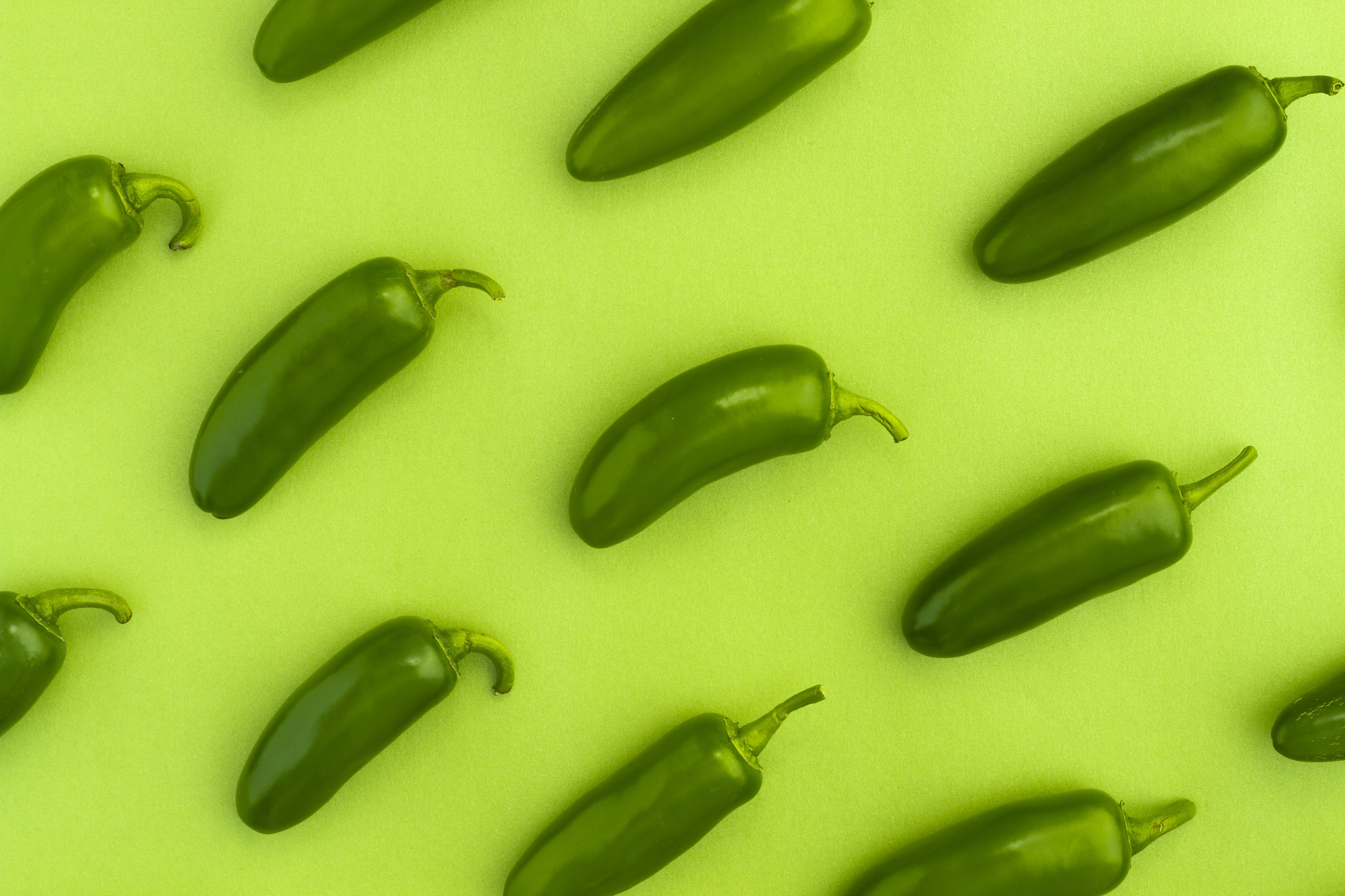Jalapeno peppers on green background