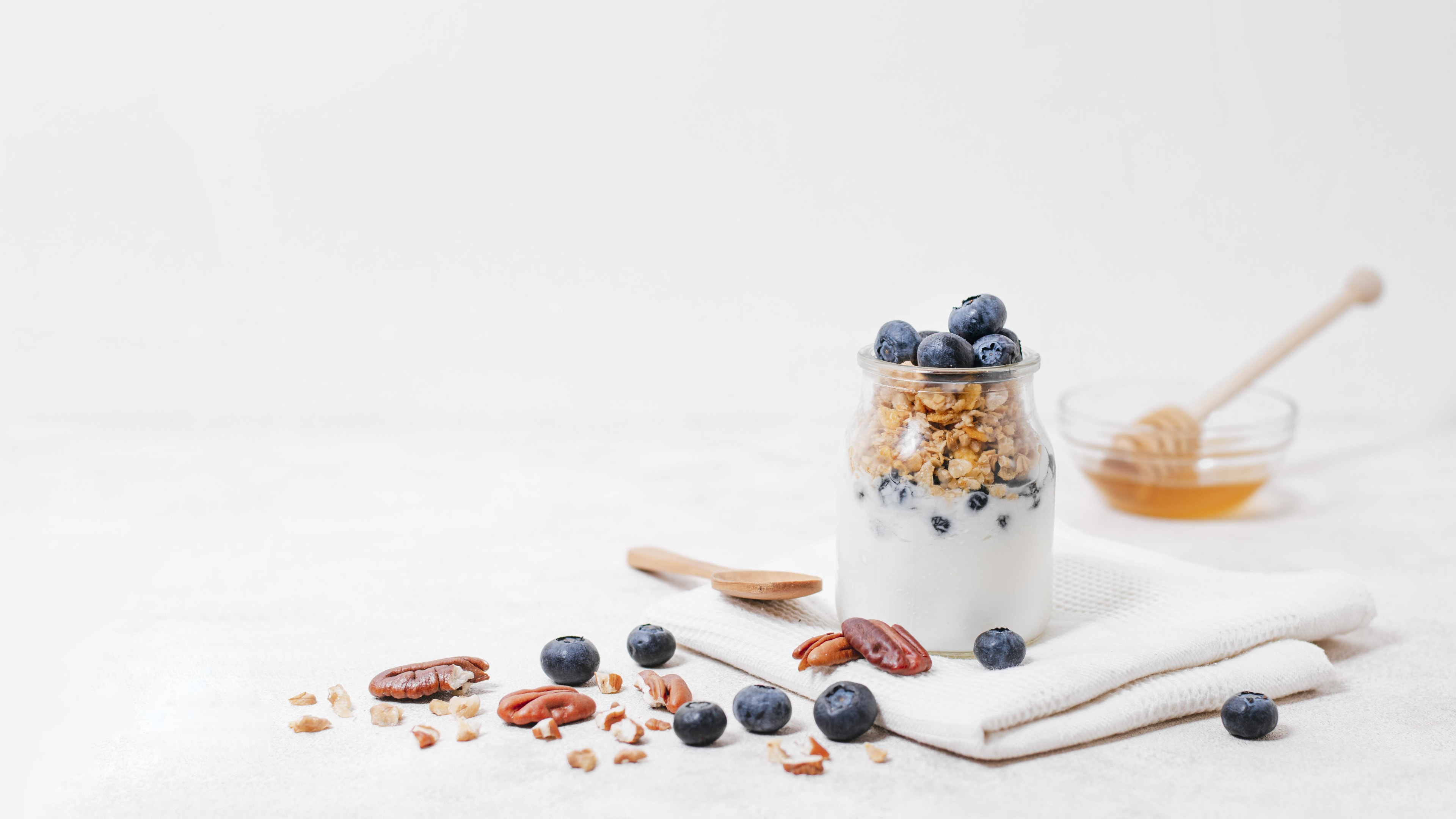 Jar filled with yogurt, granola and blueberries