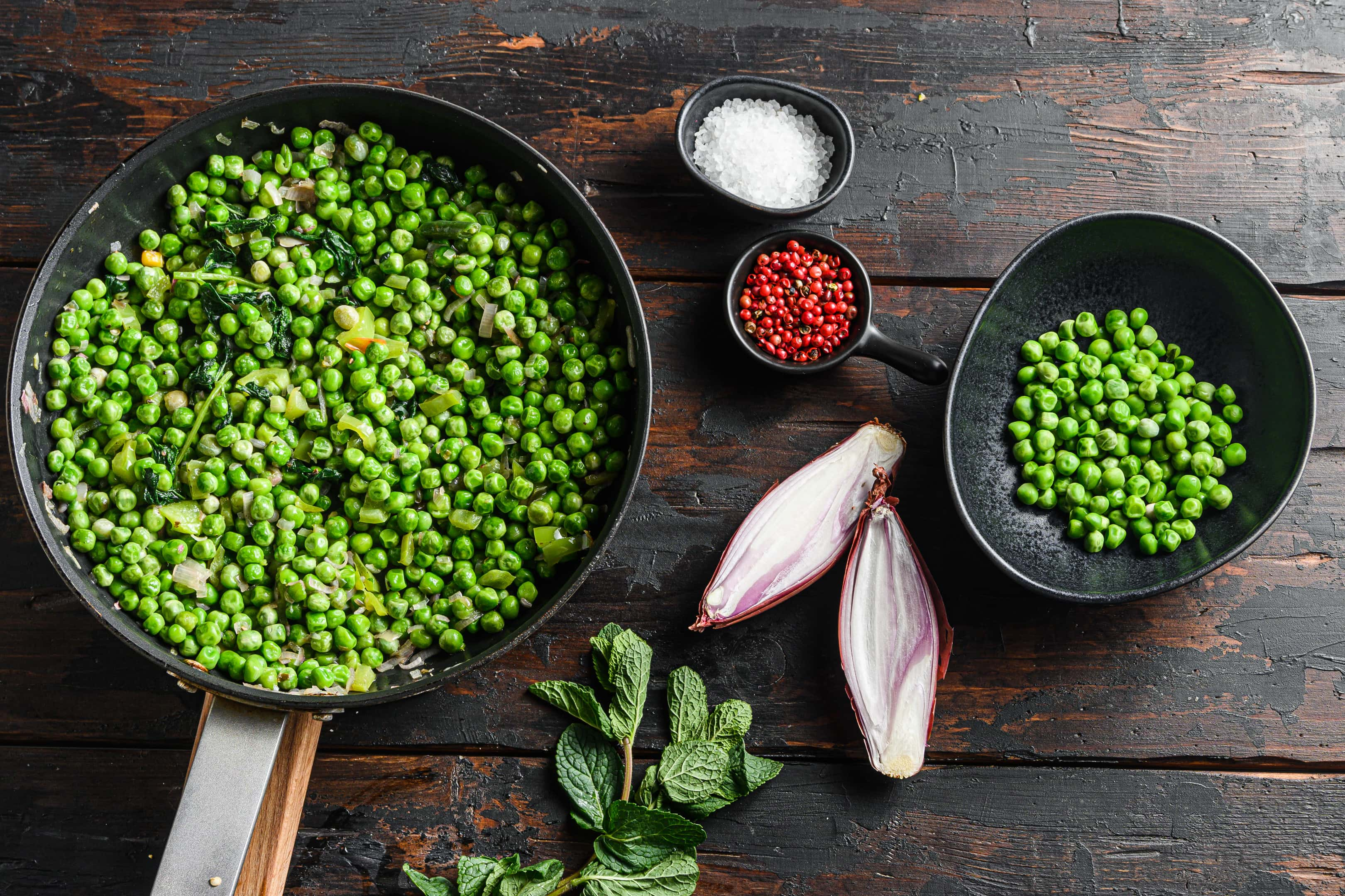 Large pan of cooked peas on wooden table