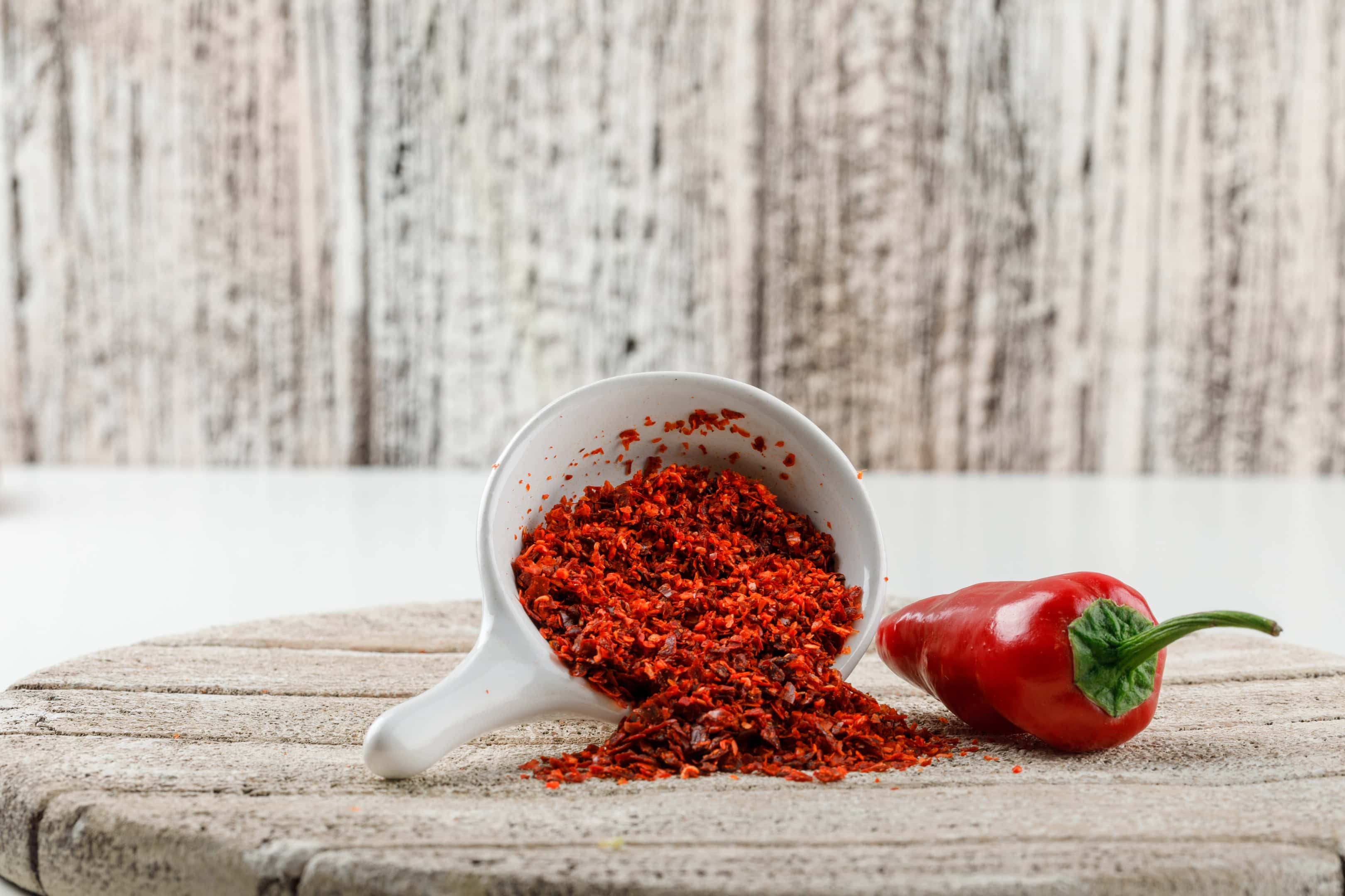 Paprika powder with red paprika pepper on wooden board