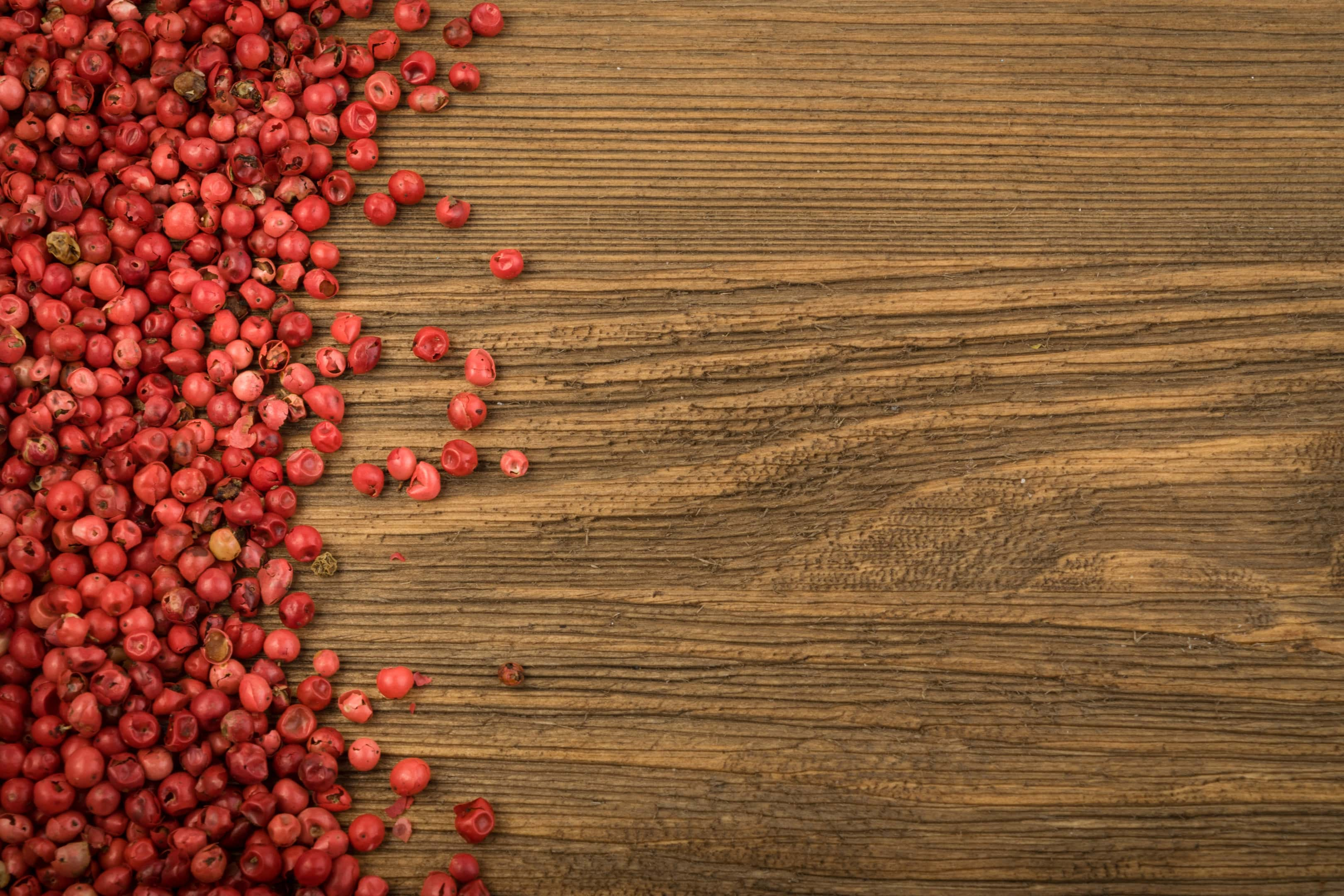 Pink peppercorn on wooden table