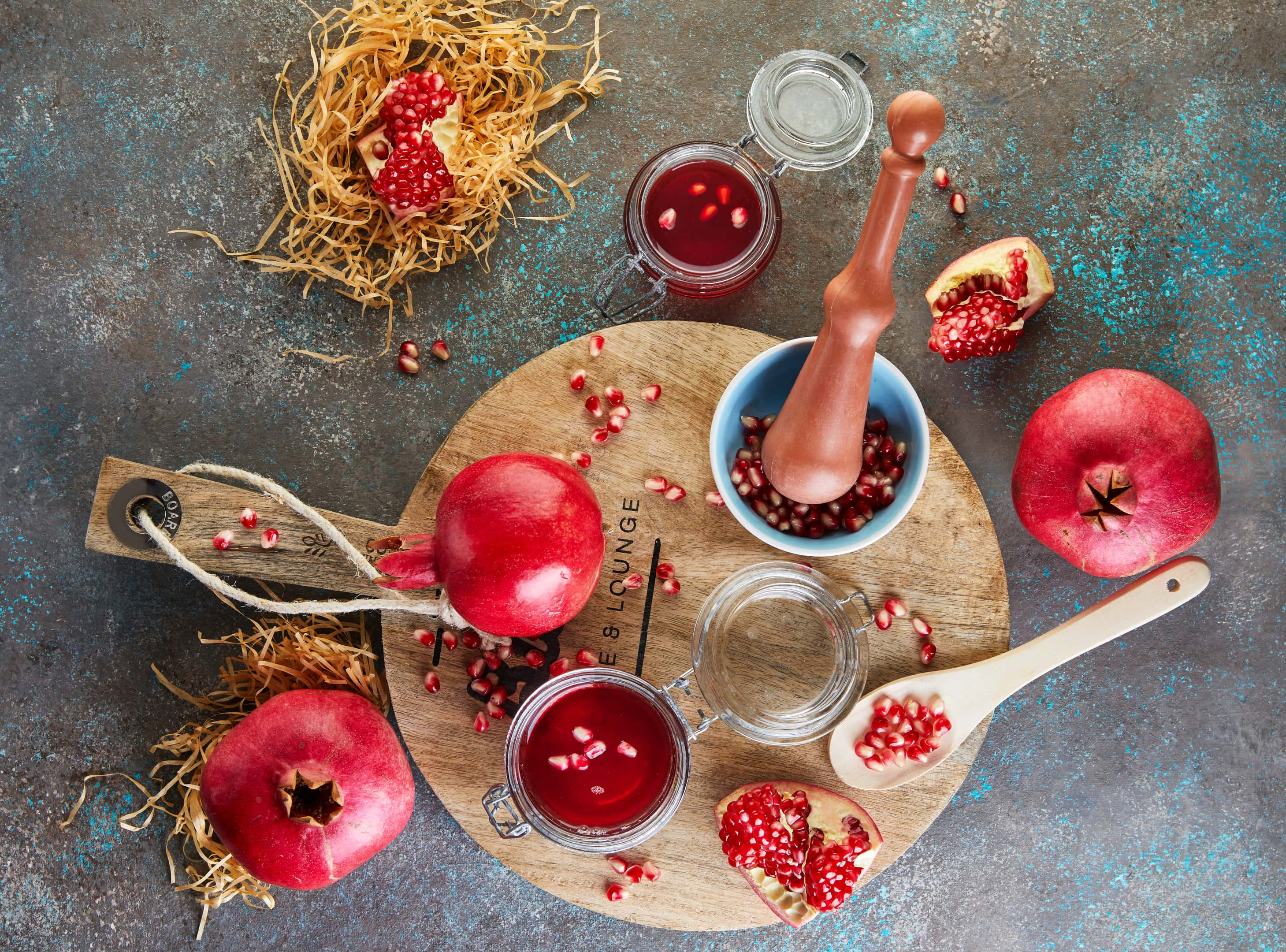Homemade pomegranate molasses syrup in jars with pomegranate seeds on a wooden board
