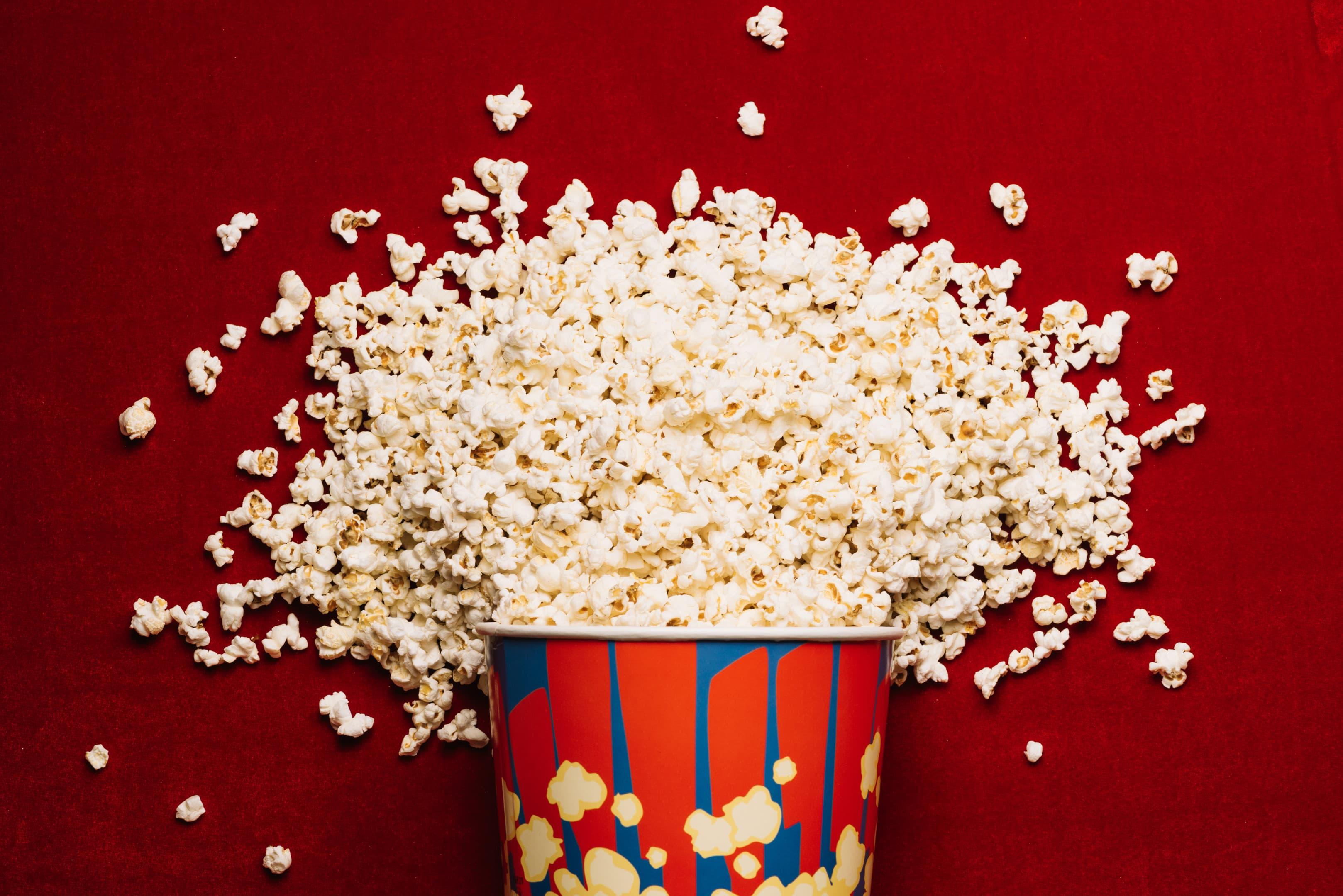 Popcorn spilled from striped bucket on cinema floor