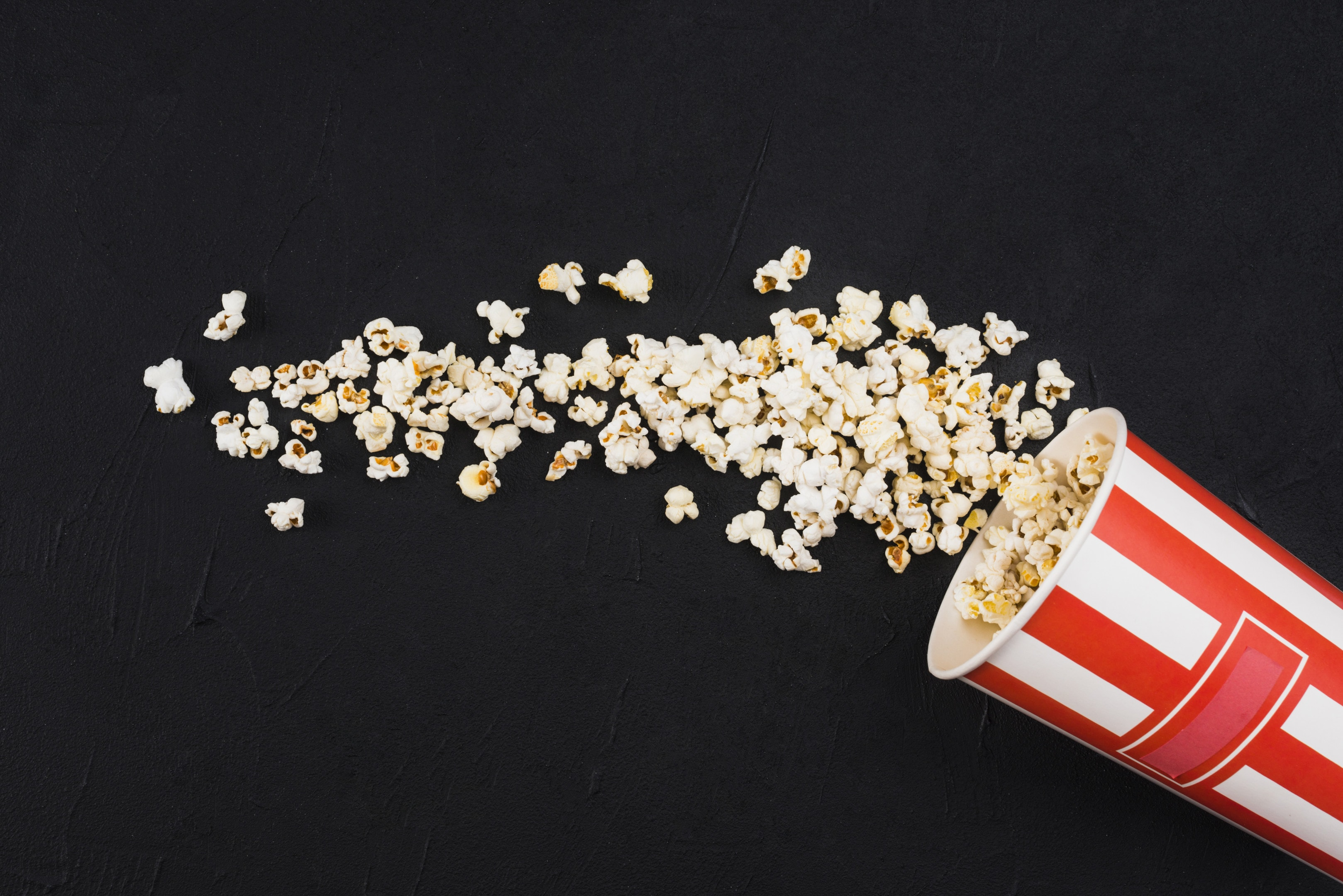 Popcorn spilled from striped on black background
