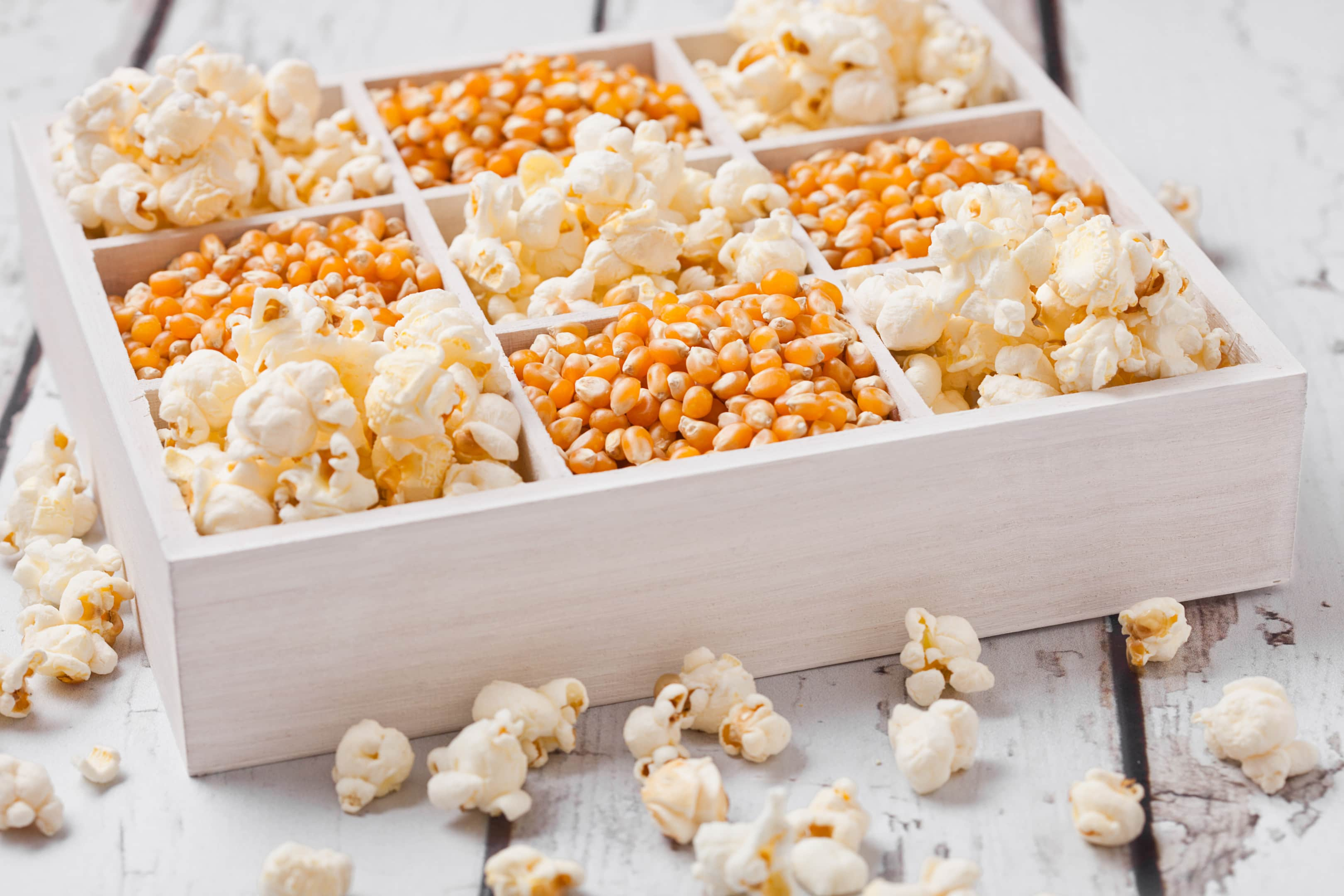Raw corn seeds and popcorn in white wooden box