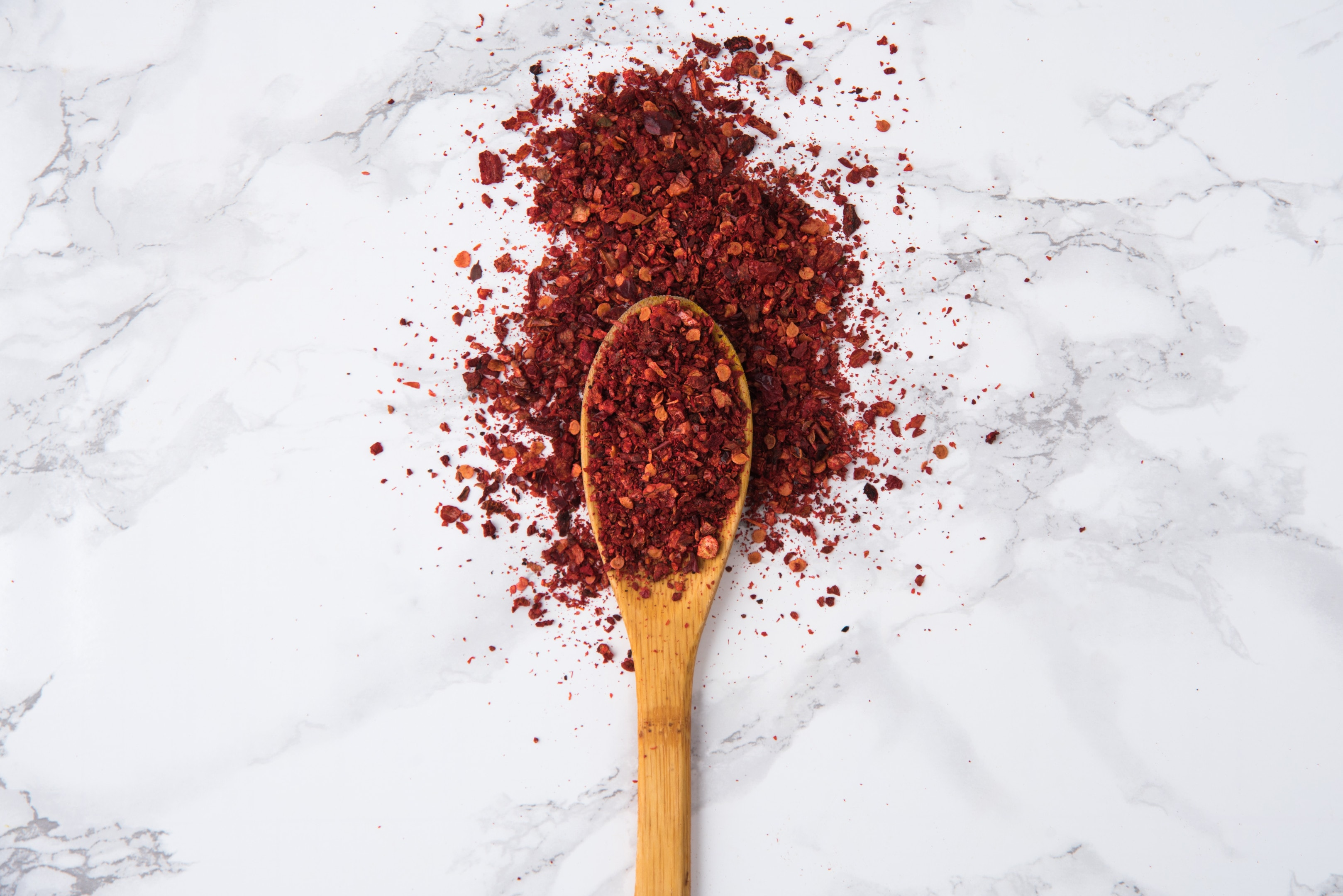 Red hot chilli pepper crushed flakes on wooden spoon