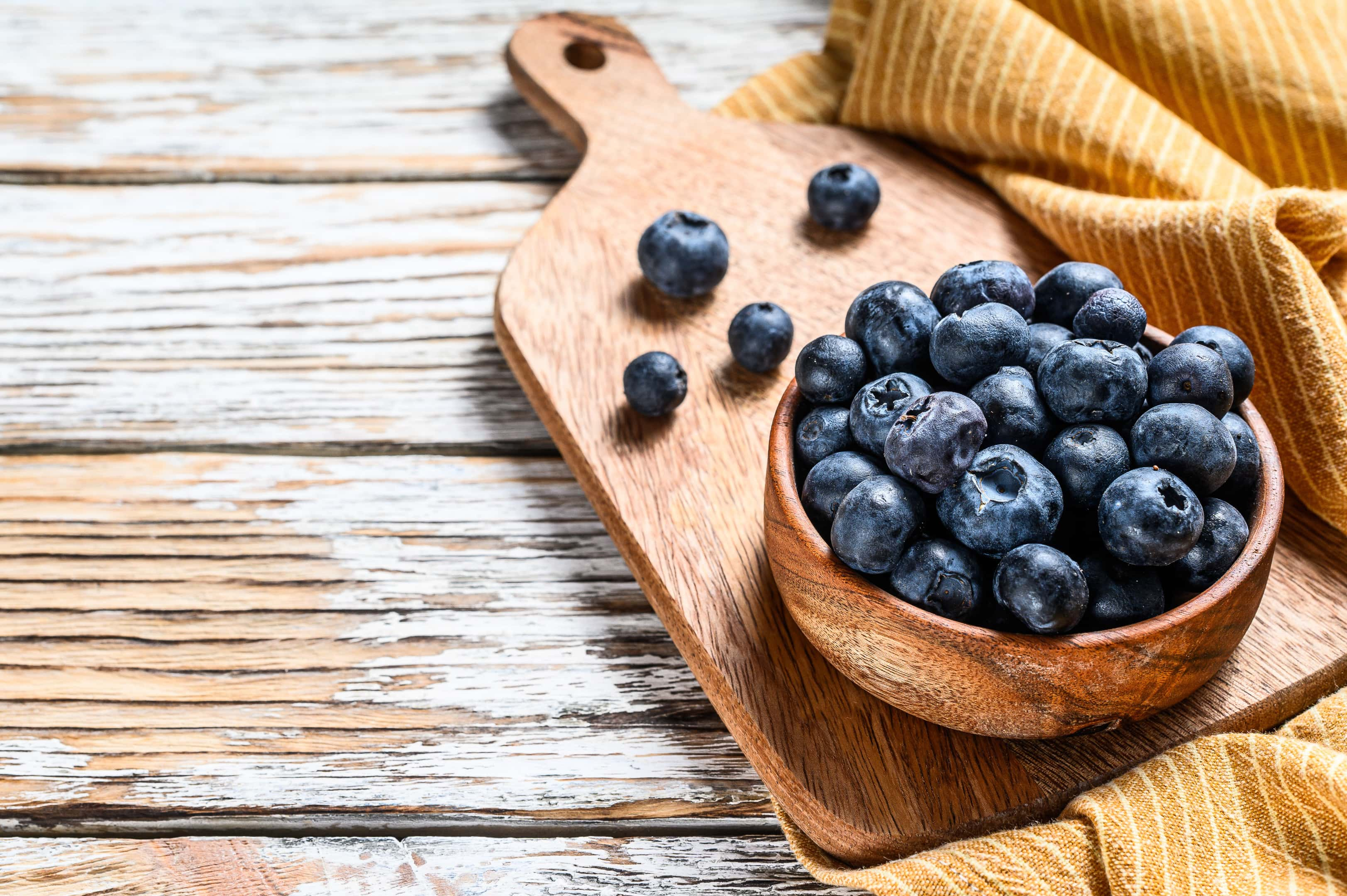 Ripe blueberries in a wooden bowl on a wooden board