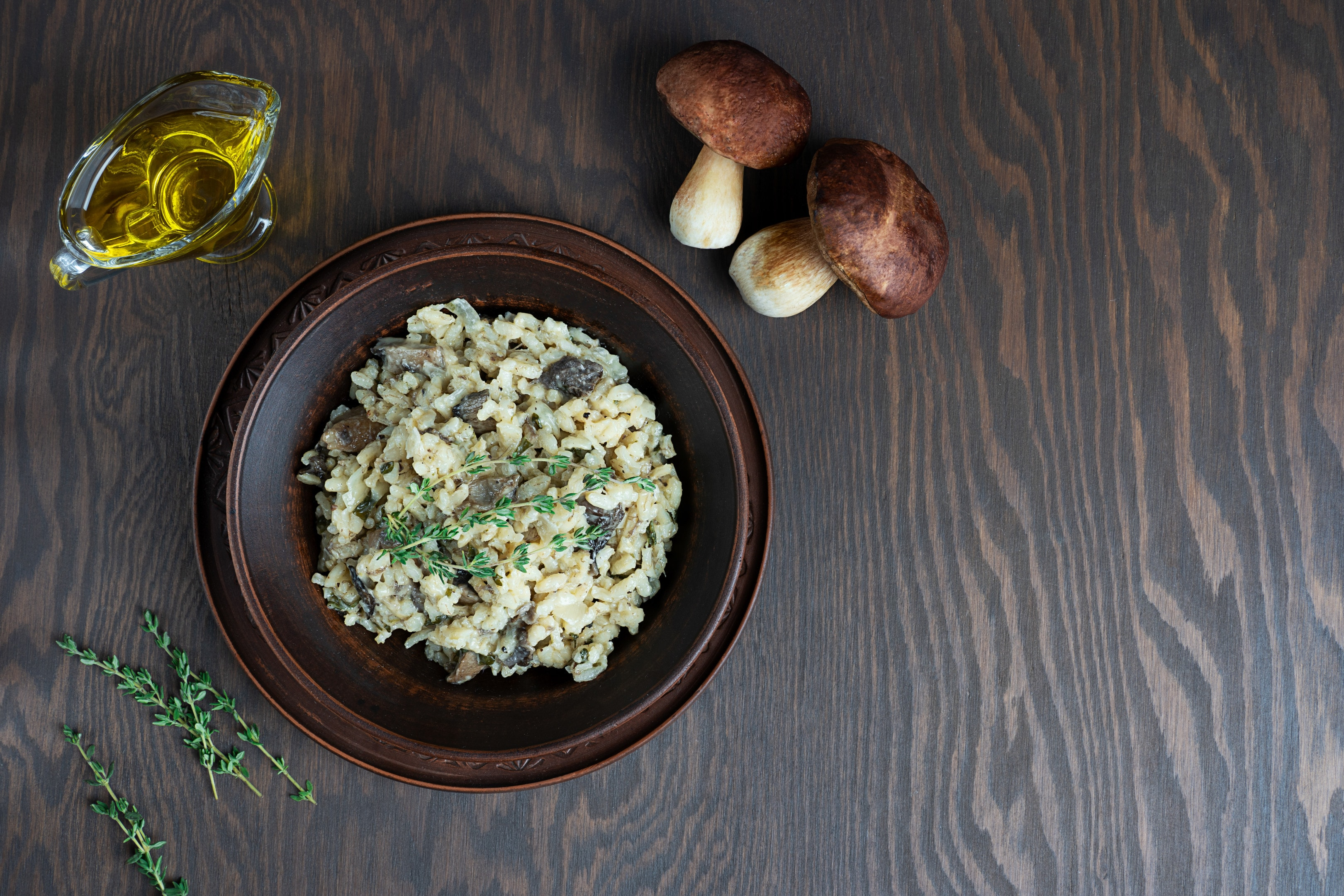 Risotto with arborio rice broth mushrooms thyme on wooden table
