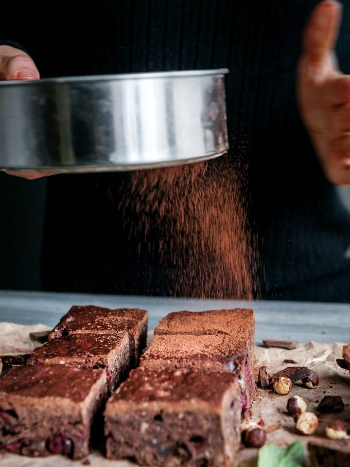 Sprinkling cacao on homemade chocolate chickpea brownie vegan and gluten-free