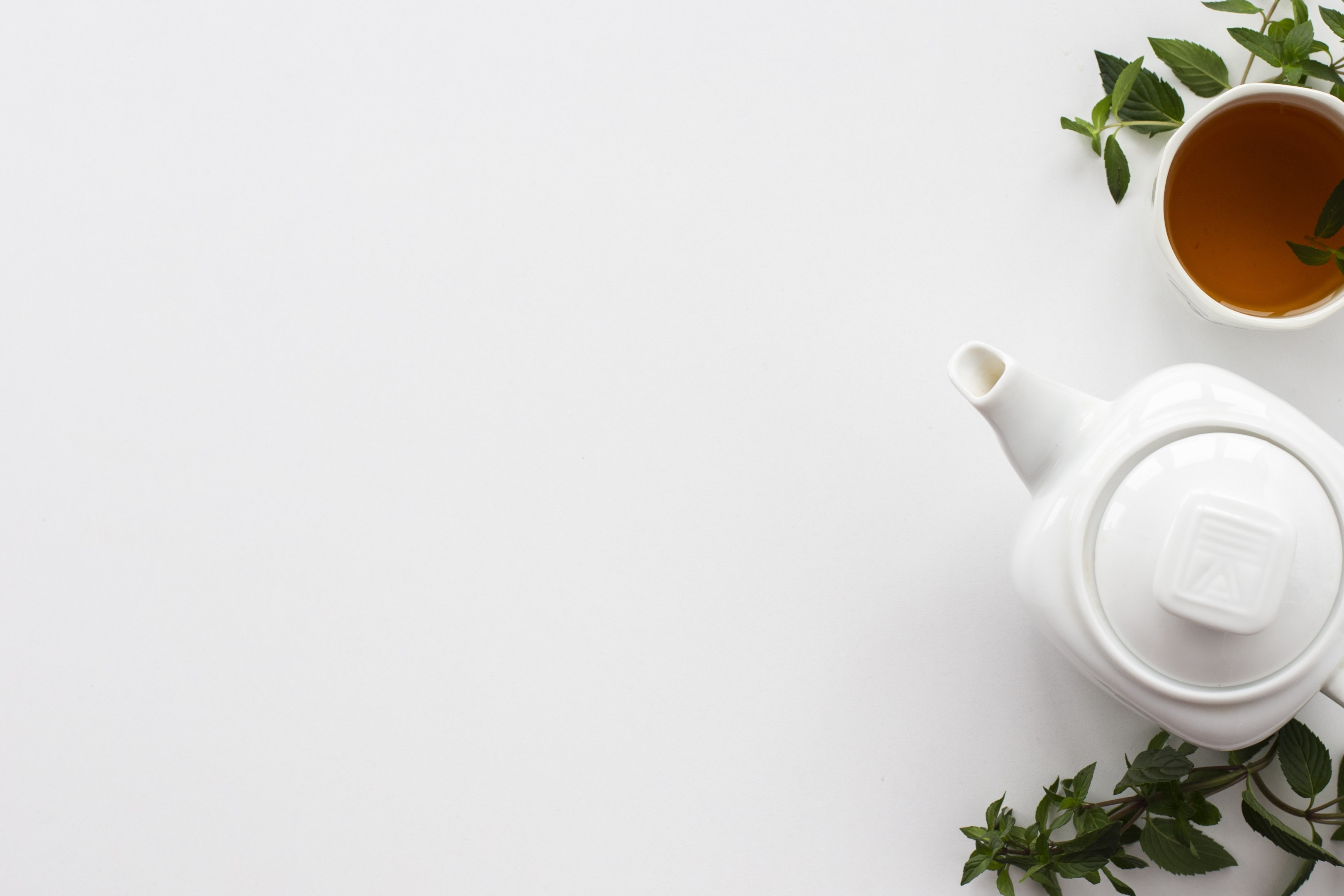 Teapot and cup of white tea with mint leaves