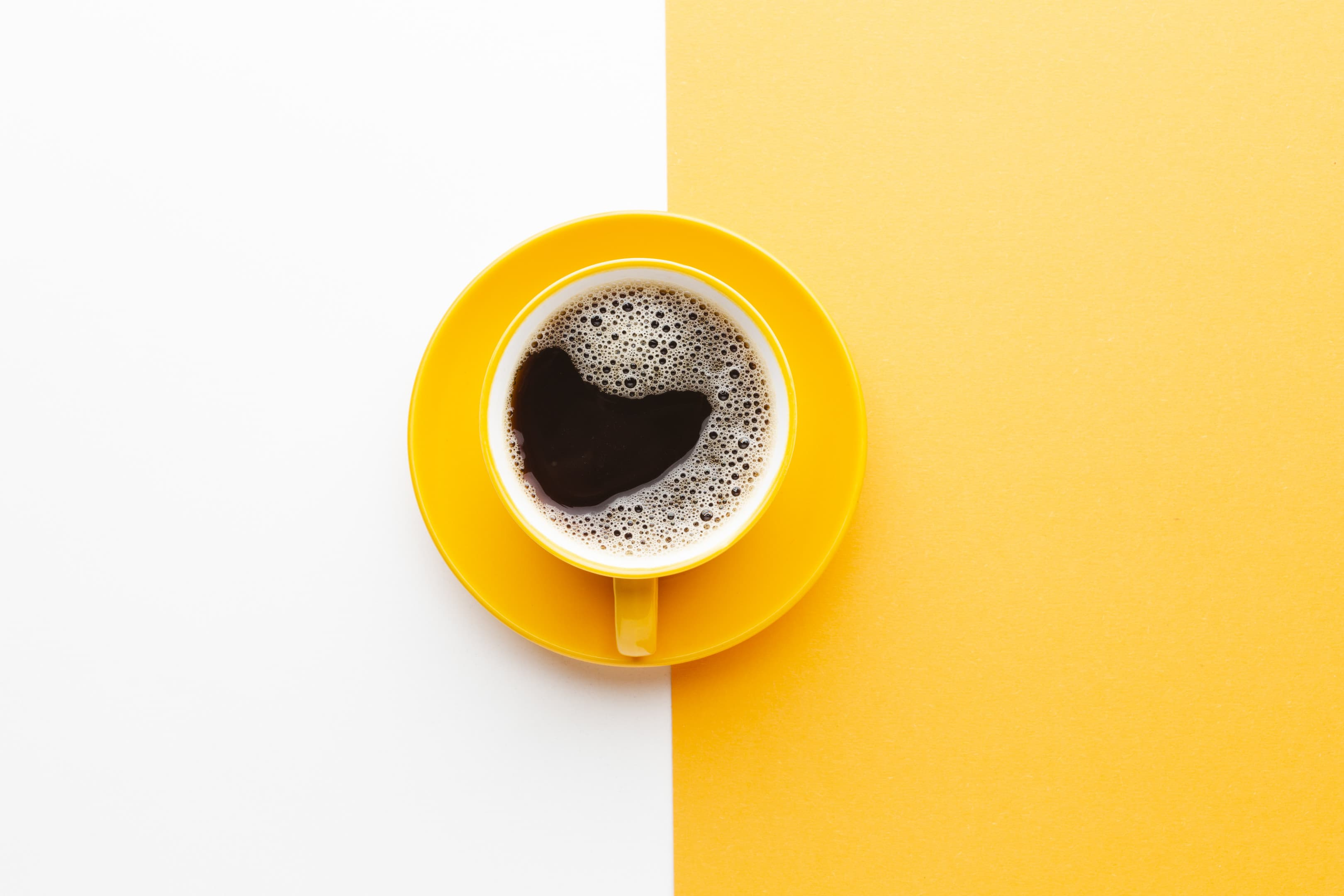 Top view fresh cup of coffee on white and yellow background