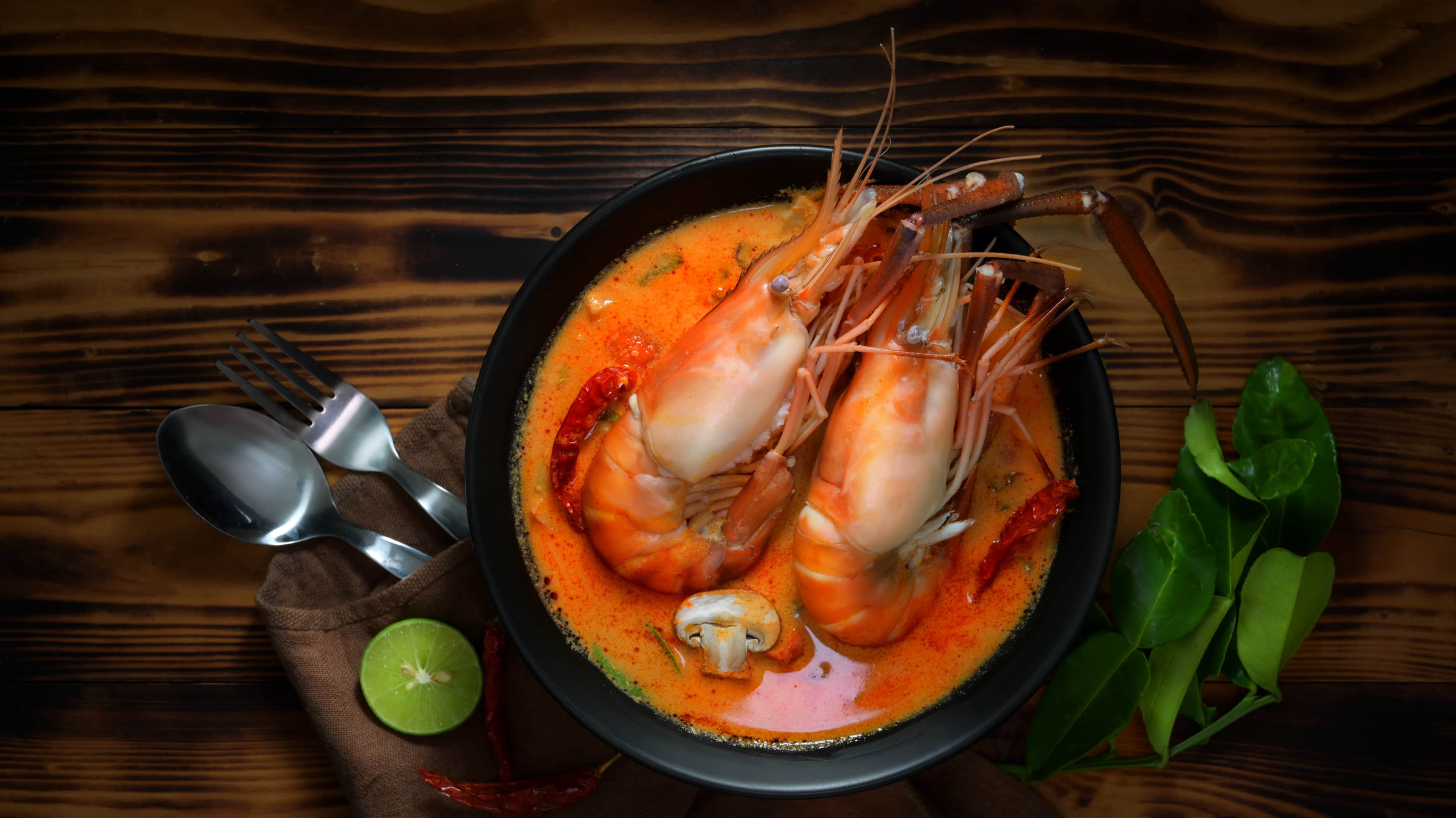 Top view of Tom yum goong with prawns, spicy soup in black bowl on wooden table