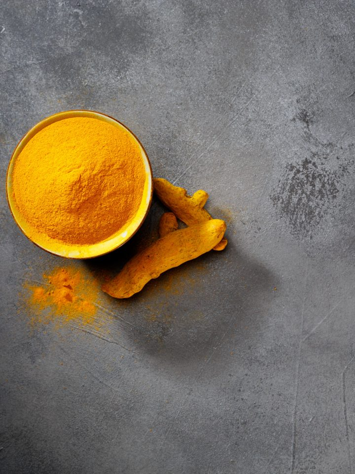Turmeric powder and fresh turmeric on grey background.