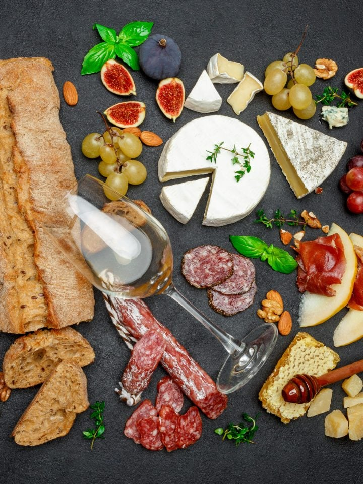 Various types of cheese, meat, fruits and wine on table