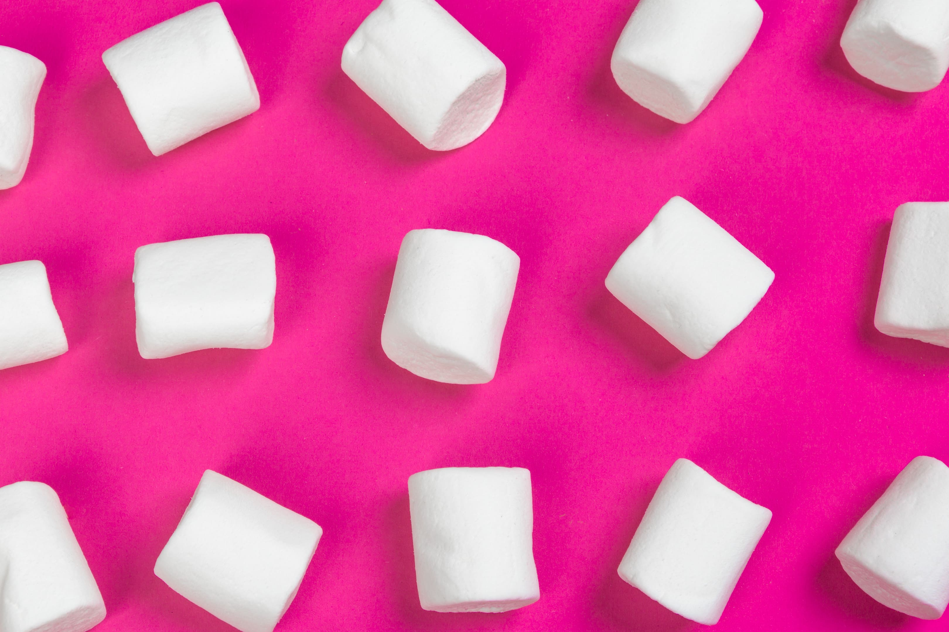 White marshmallows on a pink background
