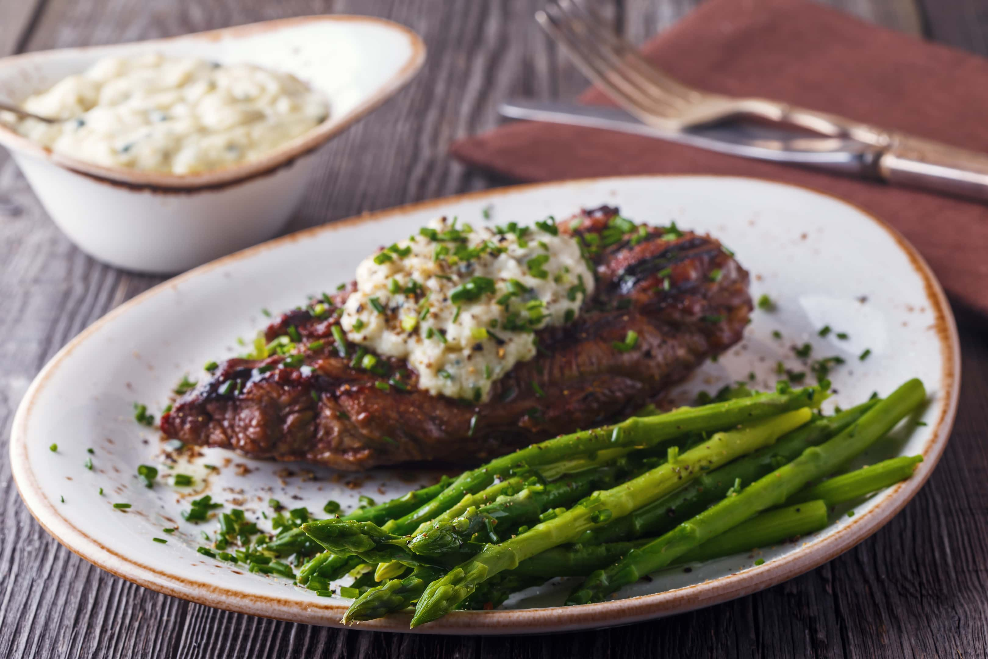 Xavier steak with cheese sauce served with asparagus