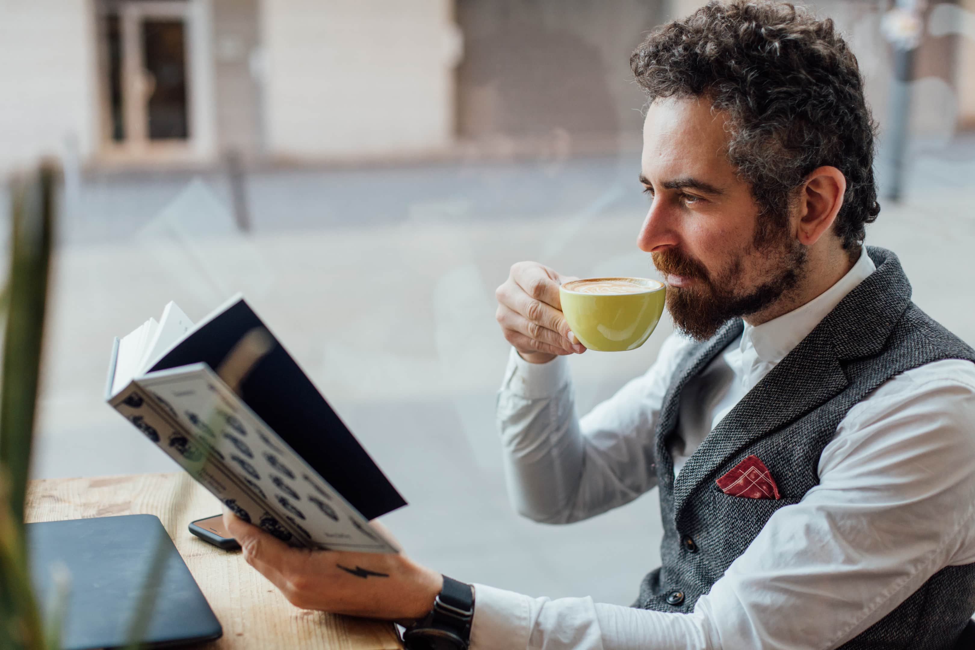 adult middle aged man sips coffee while reading interesting book