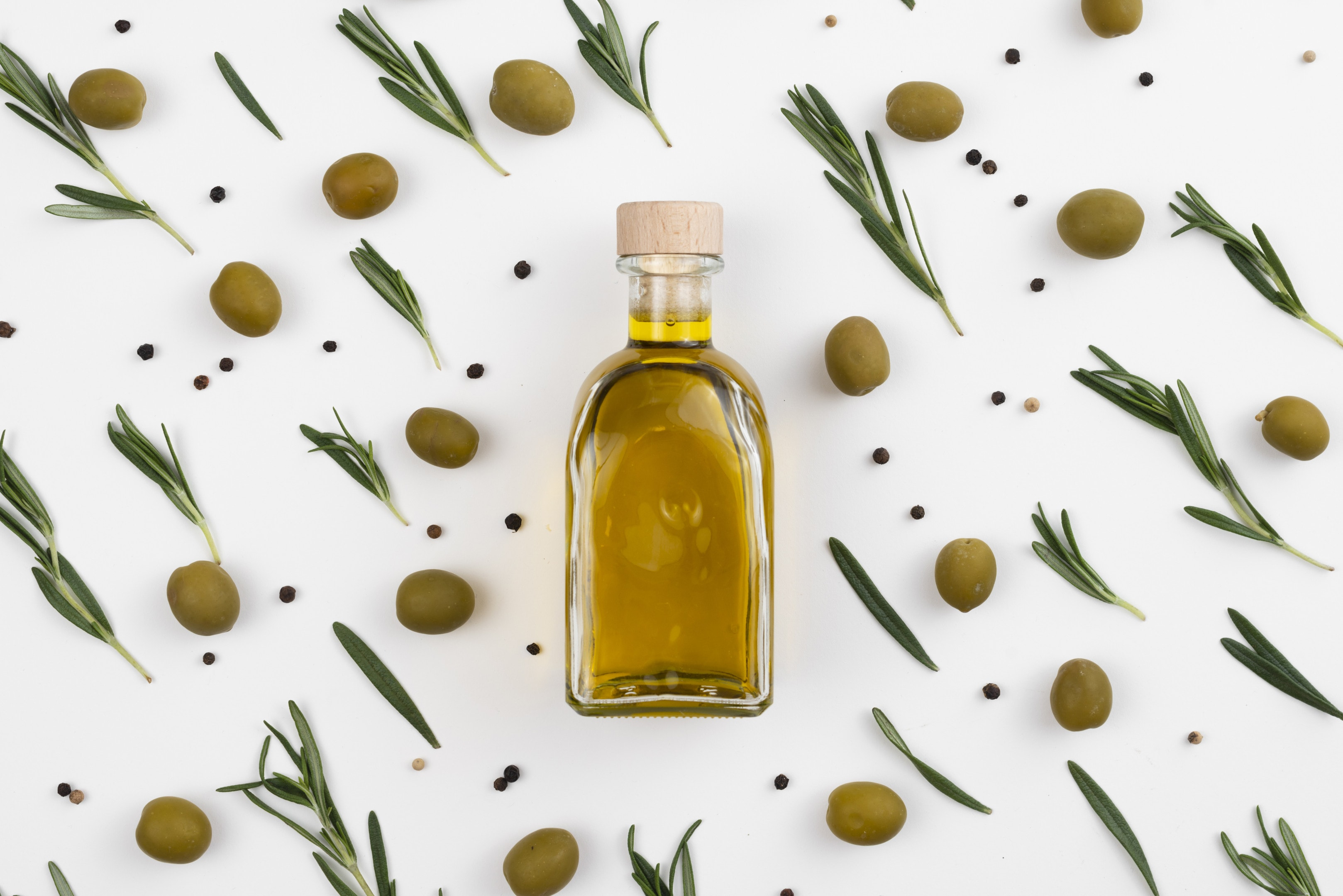 Arrangement of olive leaves and olive oil bottle on white background