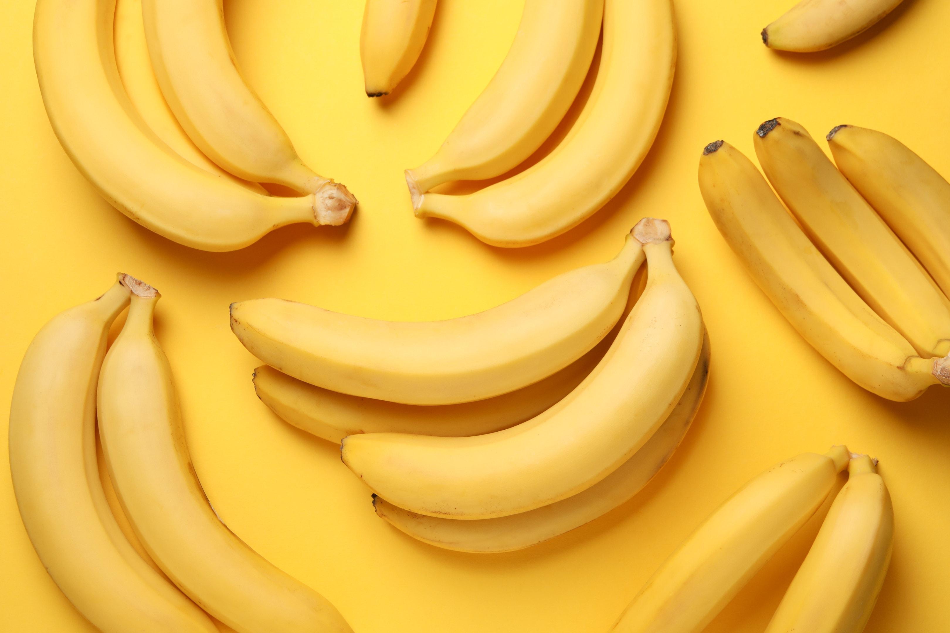 Banana clusters on yellow table