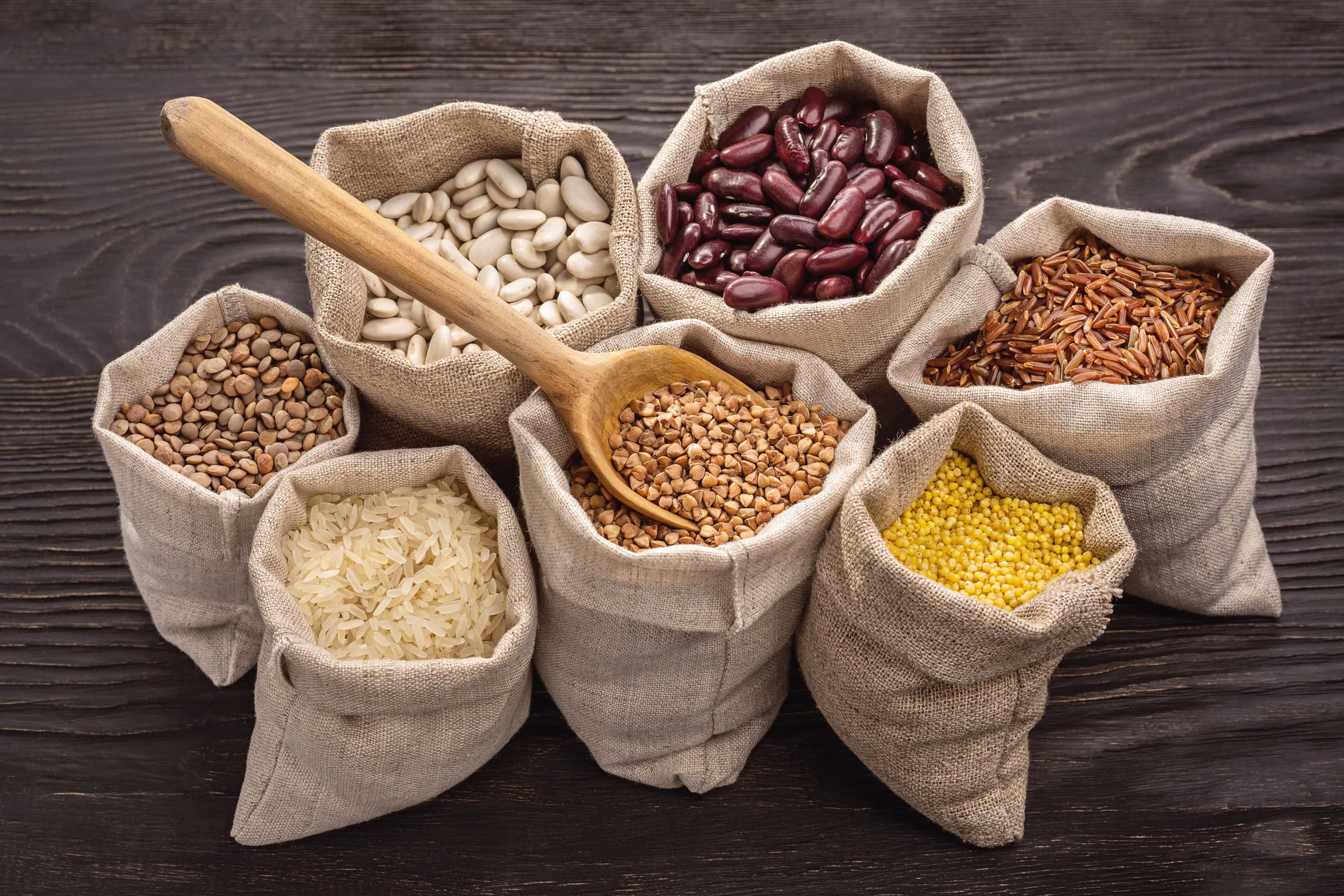Beans and legumes in bags on wooden background