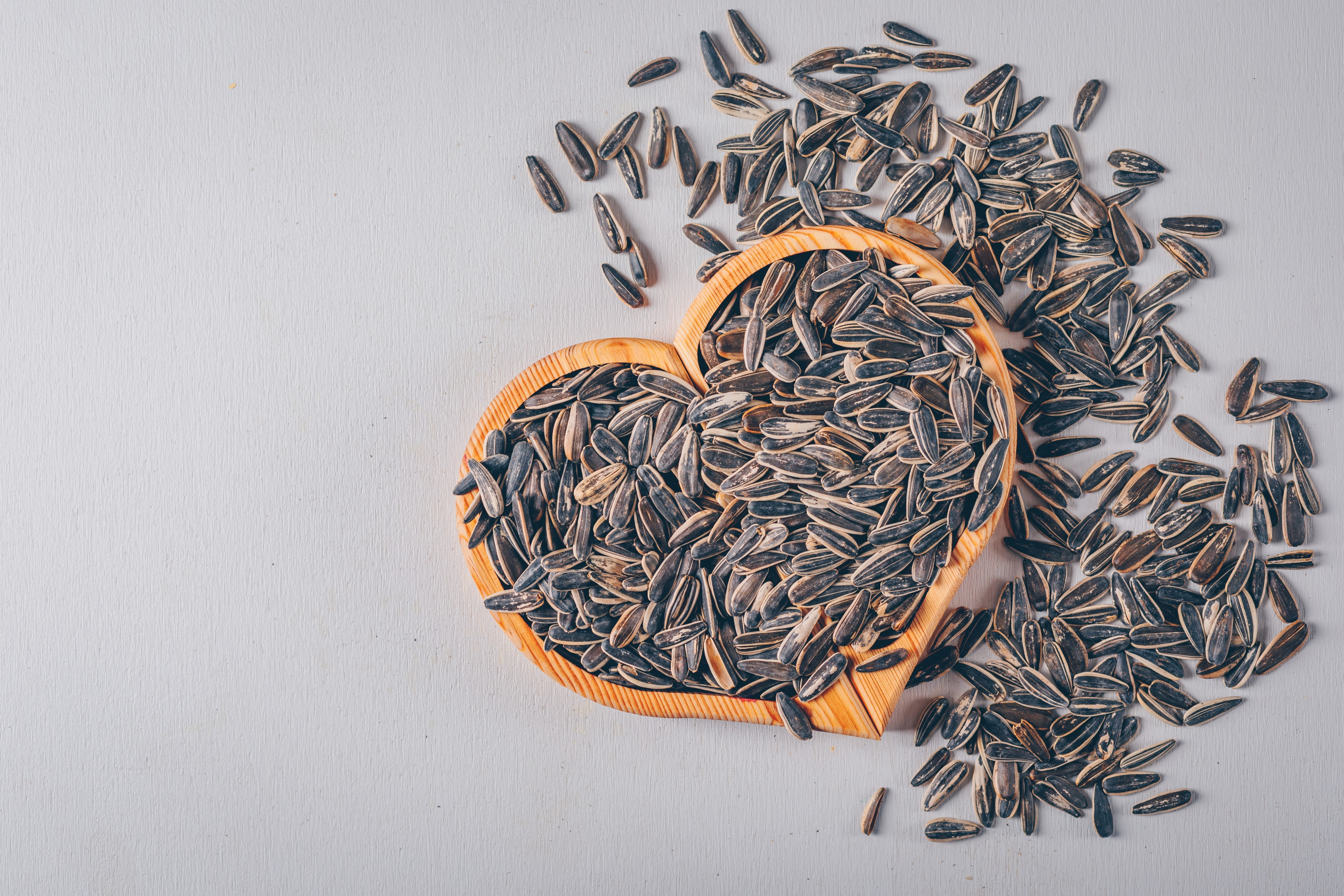 Black sunflower seeds on heart shaped board on gray background