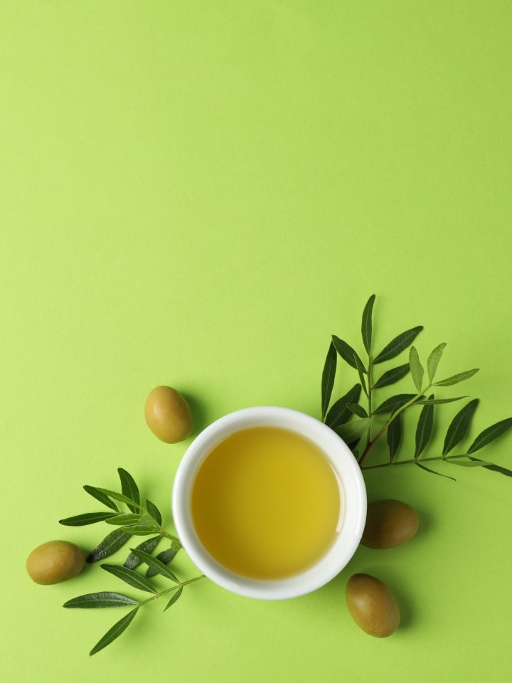 Bowl with olive oil and olives and olive leaves on green background
