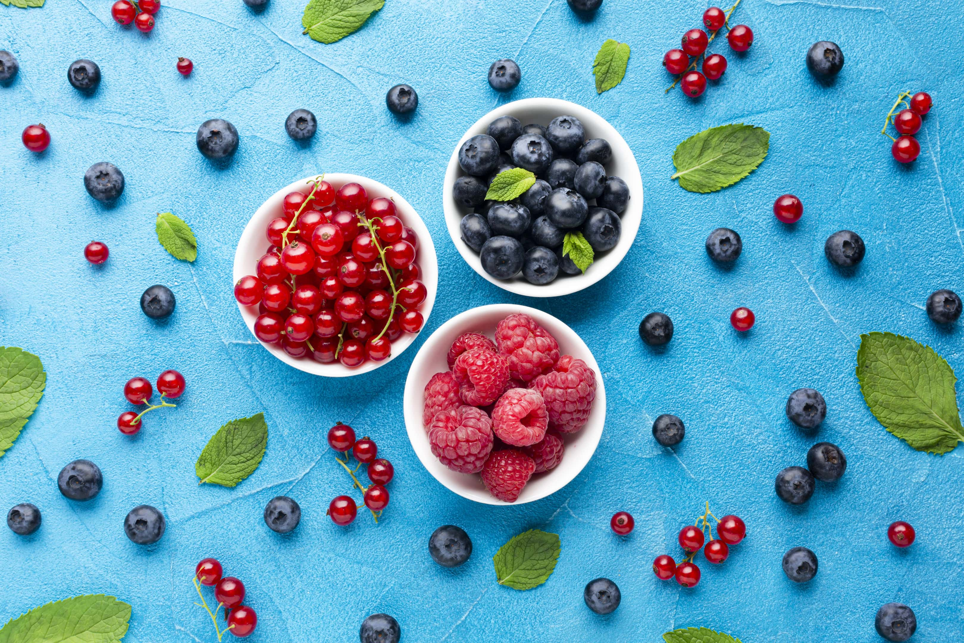 Bowls of fresh berries on blue background