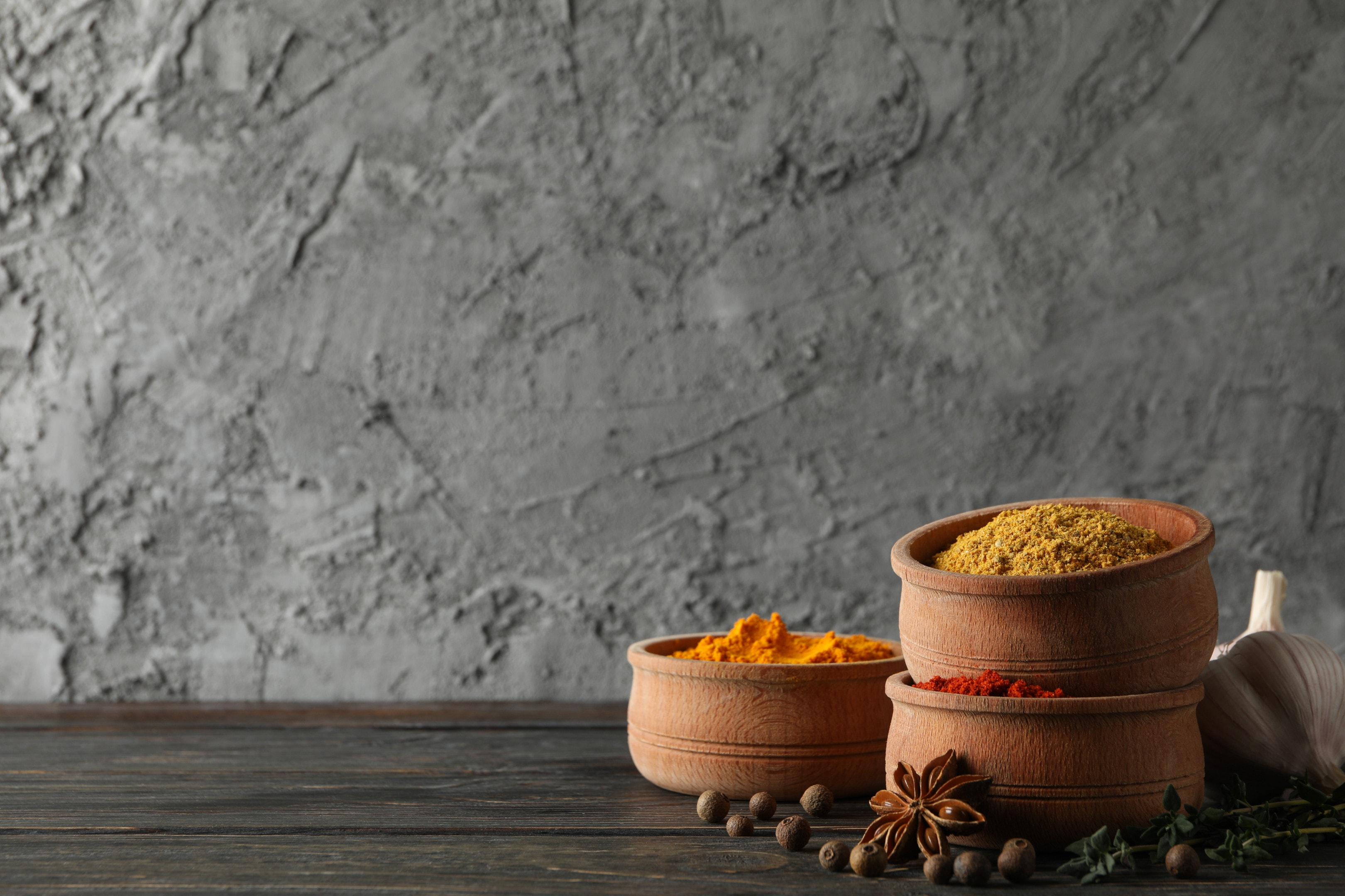 Bowls with different masala curry powders on wooden background