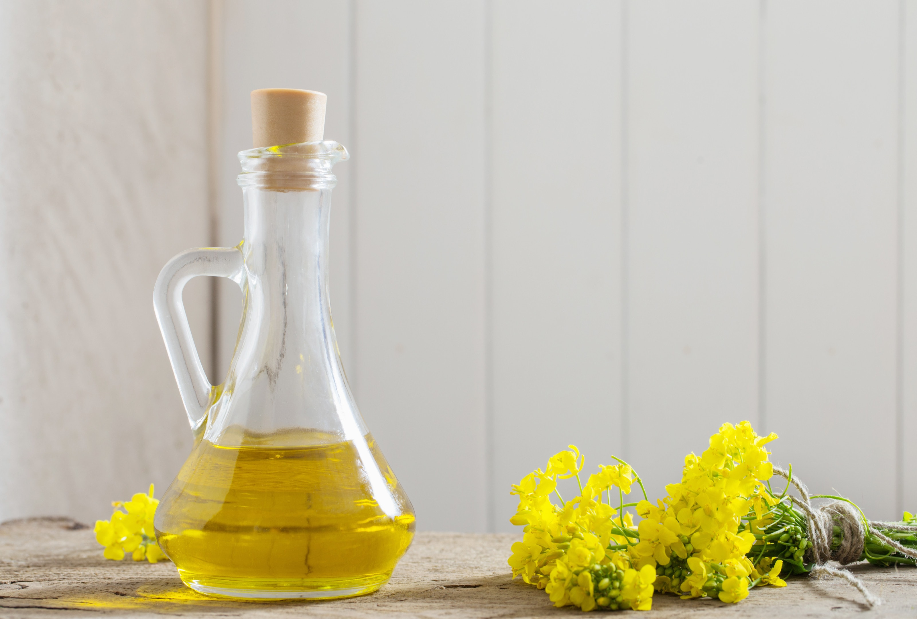 Canola oil with rape flowers on wooden table